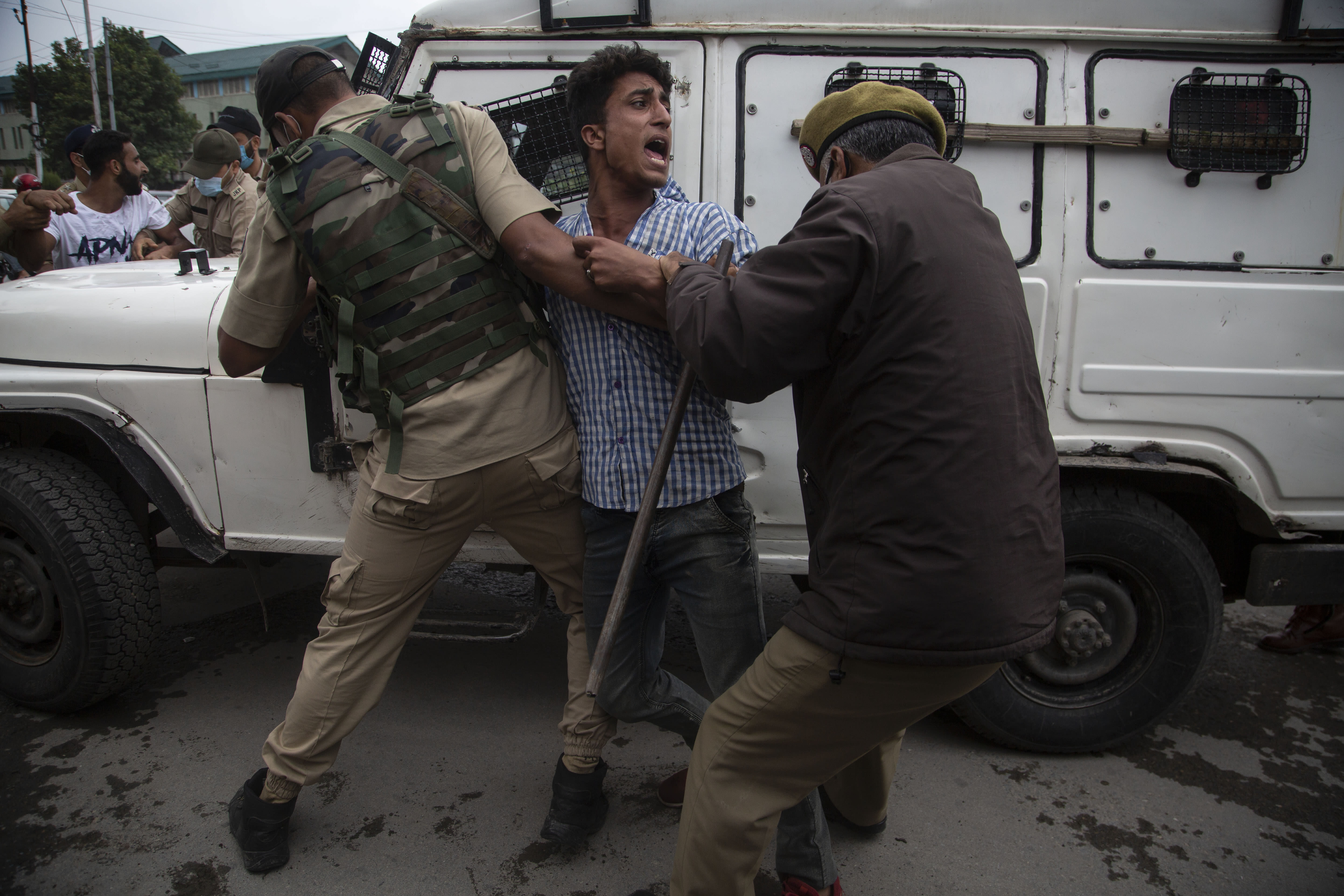 Indian policemen detain a Kashmiri Shiite Muslim as he attempts with others to take out a religious procession in Srinagar, Indian controlled Kashmir, Friday, Aug. 28, 2020. Police and paramilitary soldiers on Friday detained dozens of Muslims participating in religious processions in the Indian portion of Kashmir. Authorities had imposed restrictions in parts of Srinagar, the region's main city, to prevent gatherings marking Muharram from developing into anti-India protests. (AP Photo/Mukhtar Khan)