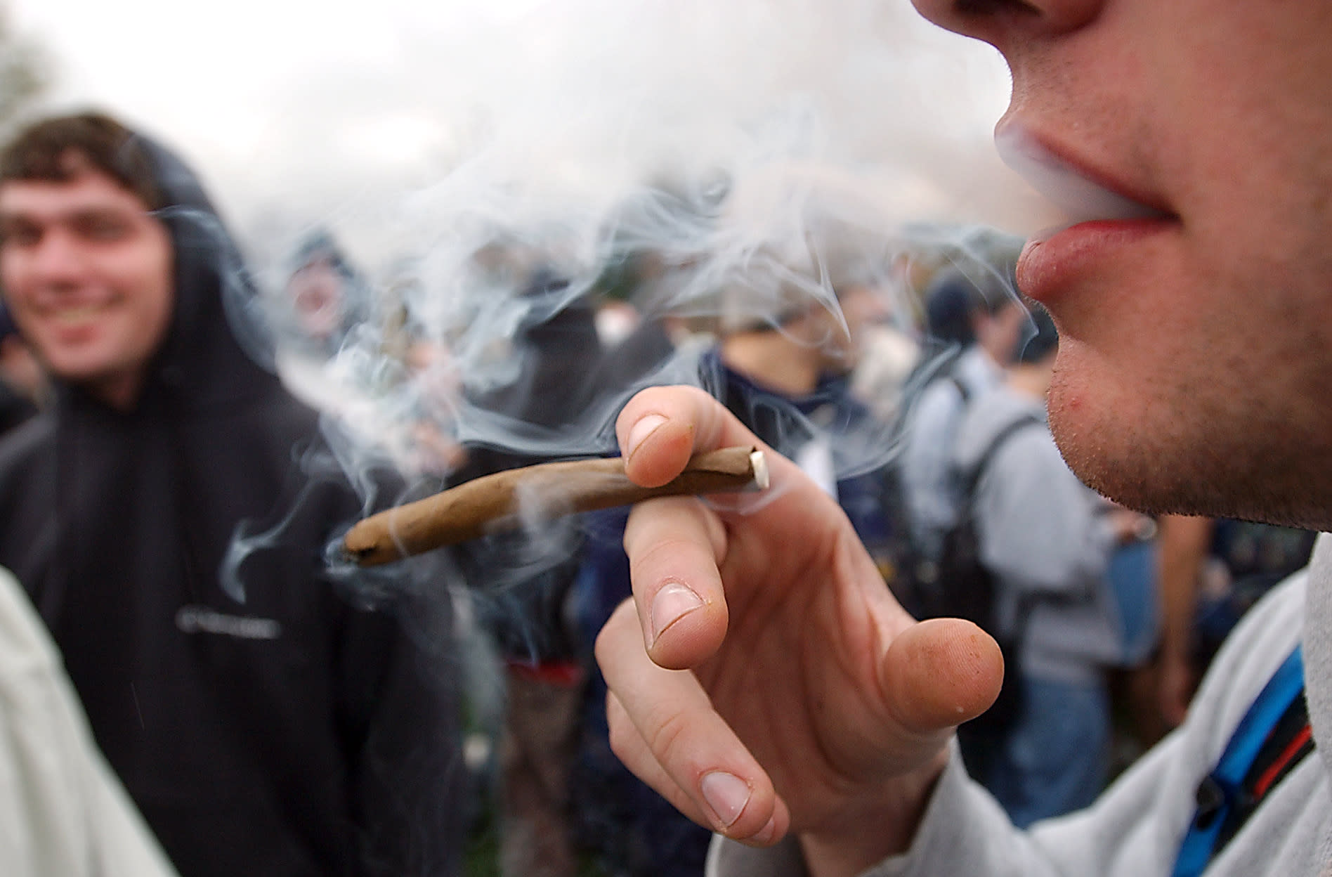 """FILE - In an April 20, 2005 file photo, a University of Colorado freshman, who did not want to be identified, joins a crowd smoking marijuana during a """"420"""" gathering at Farrand Field at the University of Colorado in Boulder, Colo. People who started using marijuana persistently before age 18 risk losing some of their IQ by the time they're 38, a long-running study says. In contrast, even long-term chronic users who started after age 18 showed no such effect, suggesting the drug holds some particular toxicity for the developing brain. (AP Photo/Longmont Daily Times-Call, Richard M. Hackett, File) MANDATORY CREDIT, MAGS OUT, NO SALES"""