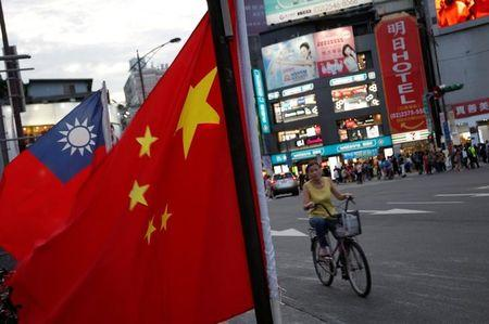 A woman rides a bike past Taiwan and China national flags during a rally held in Taipei