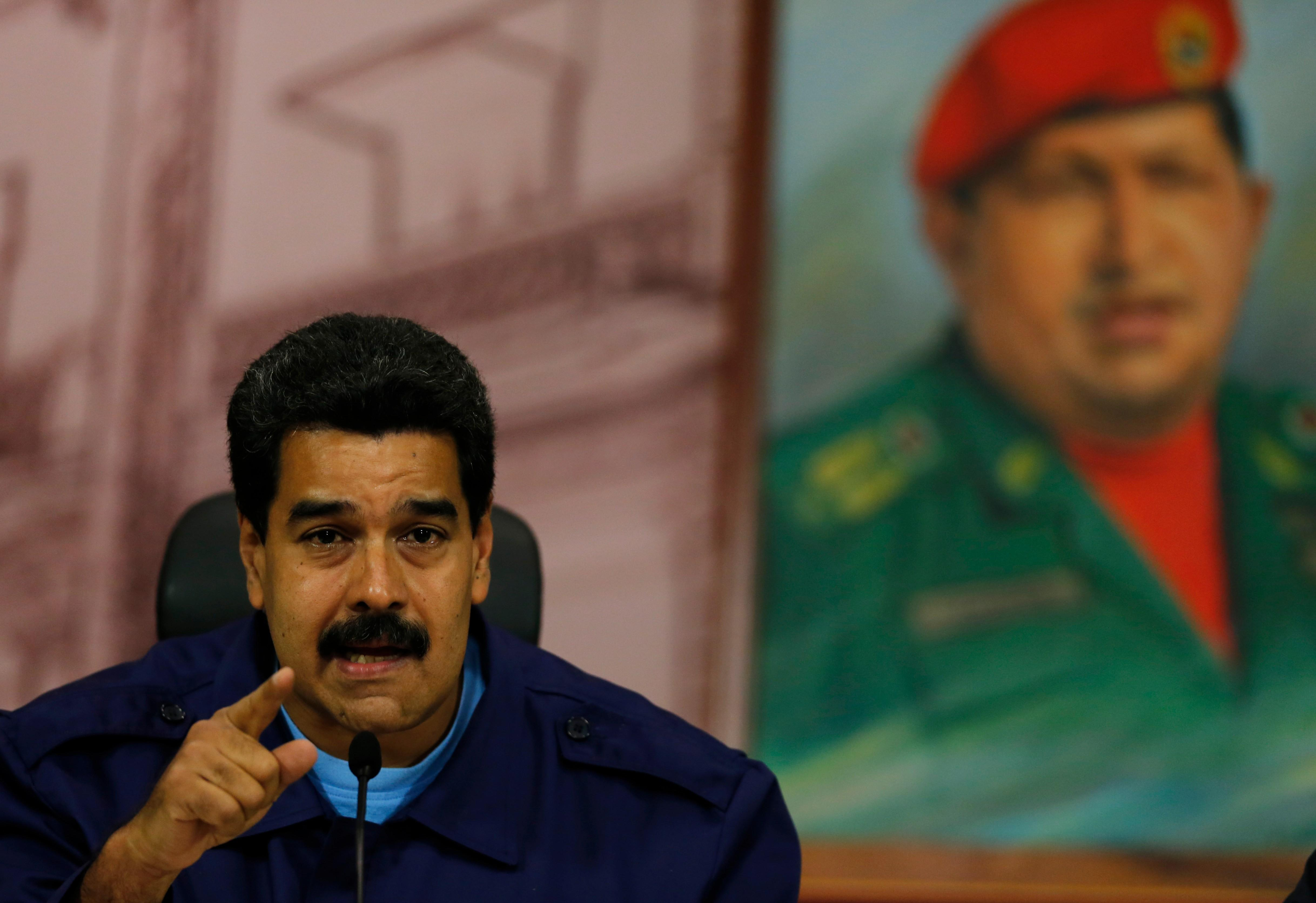 """Venezuela's President Nicolas Maduro speaks next to a painting of the late Hugo Chavez, during a news conference at Miraflores Presidential Palace in Caracas, Venezuela, Friday, Feb. 21, 2014. Speaking Friday to international media, Maduro called out what he said was a """"campaign of demonization to isolate the Bolivarian revolution."""" (AP Photo/Fernando Llano)"""