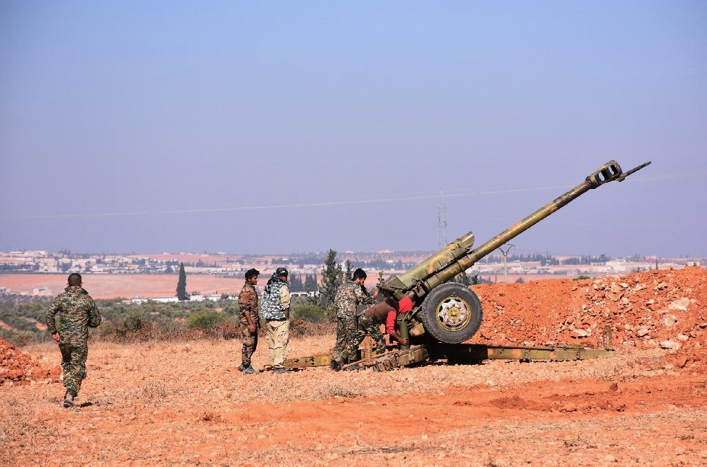 Syrian pro-government fighters fire a Russian 122mm howitzer gun as they advance in the recently recaptured village of Joubah during an offensive towards the area of Al-Bab in Aleppo province, on November 25, 2016 (AFP Photo/GEORGE OURFALIAN)