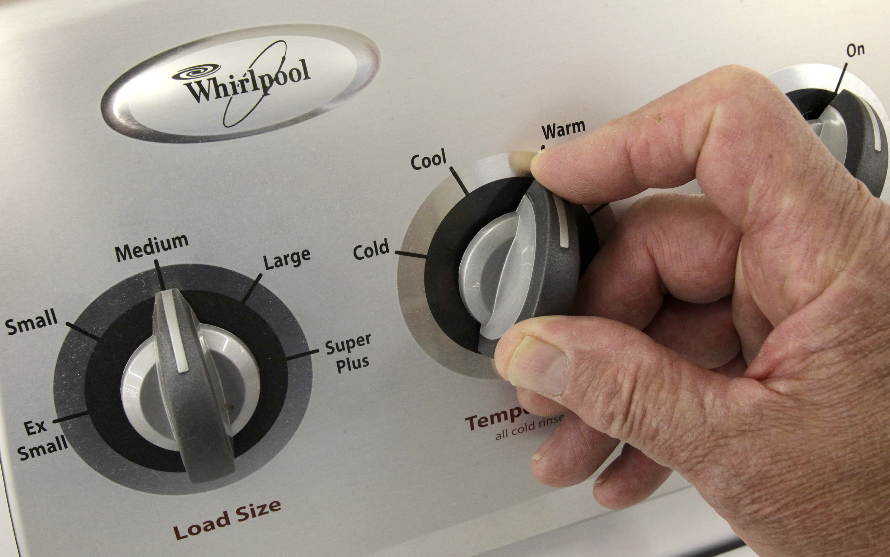 FILE - In this July 20, 2009 file photo, an unidentified employee tries the dials on a Whirlpool top load washing machine at the Sears Grand store in Solon, Ohio. Sears' Chapter 11 bankruptcy filing on Monday, Oct. 15, 2018, will have rippling effects on everything from its workers to suppliers. Suppliers in the top 20 unsecured creditors included Frigidaire, Samsung and Whirlpool, which are owed between $8 million to $23 million, according to court documents. (AP Photo/Amy Sancetta, File)