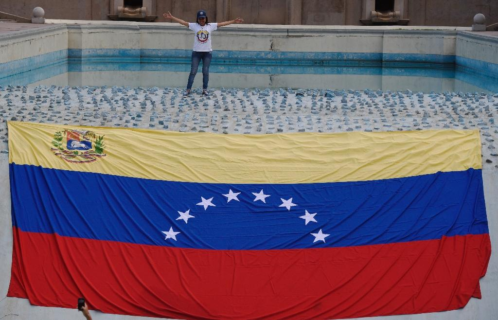 An opponent to Venenzuelan president Nicolas Maduro is seen next to a national flag before a rally in Caracas