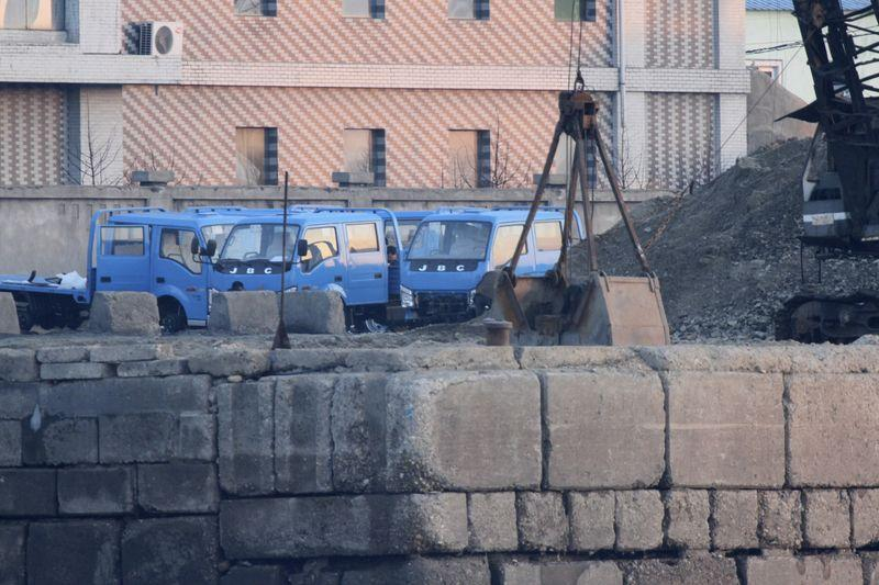 Trucks are parked next to a pile of coal on the bank of the Yalu River in Sinuiju