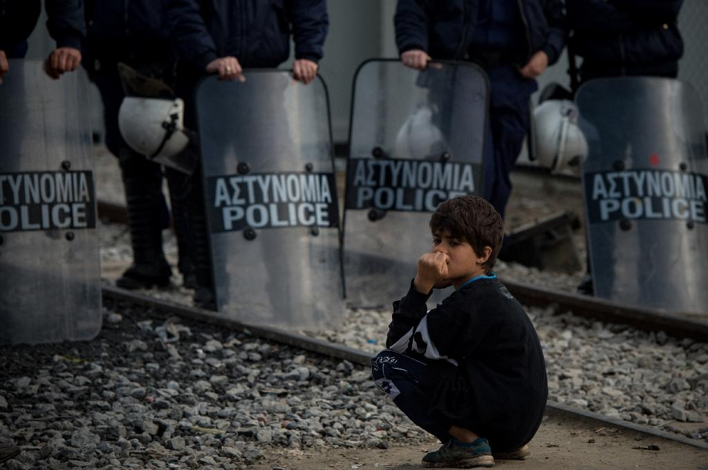 A boy crouches on railroad tracks in front of Greek border police during a protest at a makeshift camp at the Greek-Macedonian border near the village of Idomeni on March 22, 2016 (AFP Photo/Andrej Isakovic)
