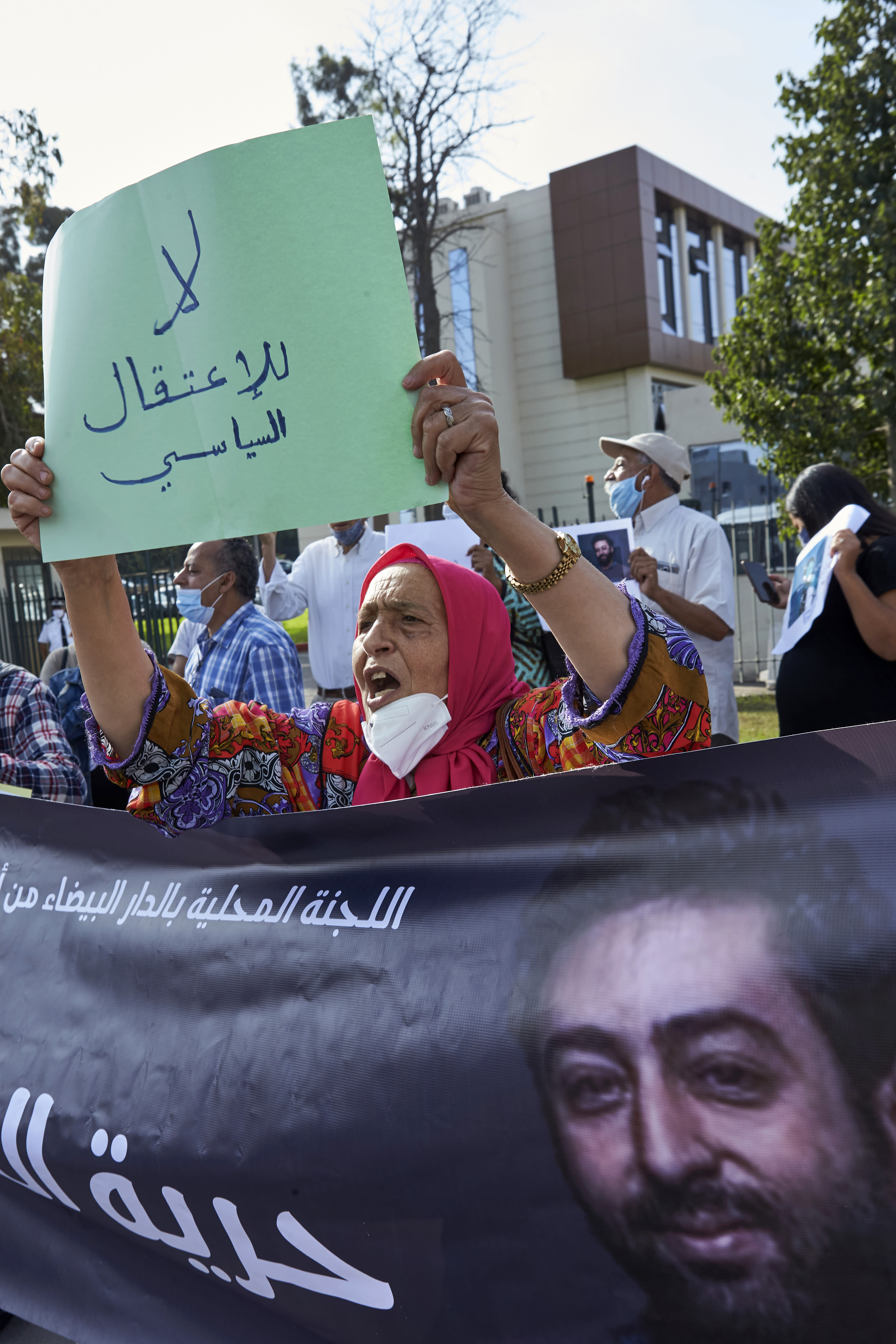 """Activist Mother Fatima holds up a banner that reads: """"No to political arrest"""", as she protests with others in front of the Casablanca Courthouse, in Casablanca, Morocco, Tuesday, Sept. 22, 2020, on the first day of the hearing of journalist and activist Omar Radi. The arrest of journalist Omar Radi follows numerous summons following a police investigation into suspicion of receiving funds linked to foreign intelligence. The investigation came after rights group Amnesty International accused Morocco of using Israeli-made spyware to snoop on its phone. (AP Photo/Abdeljalil Bounhar)"""