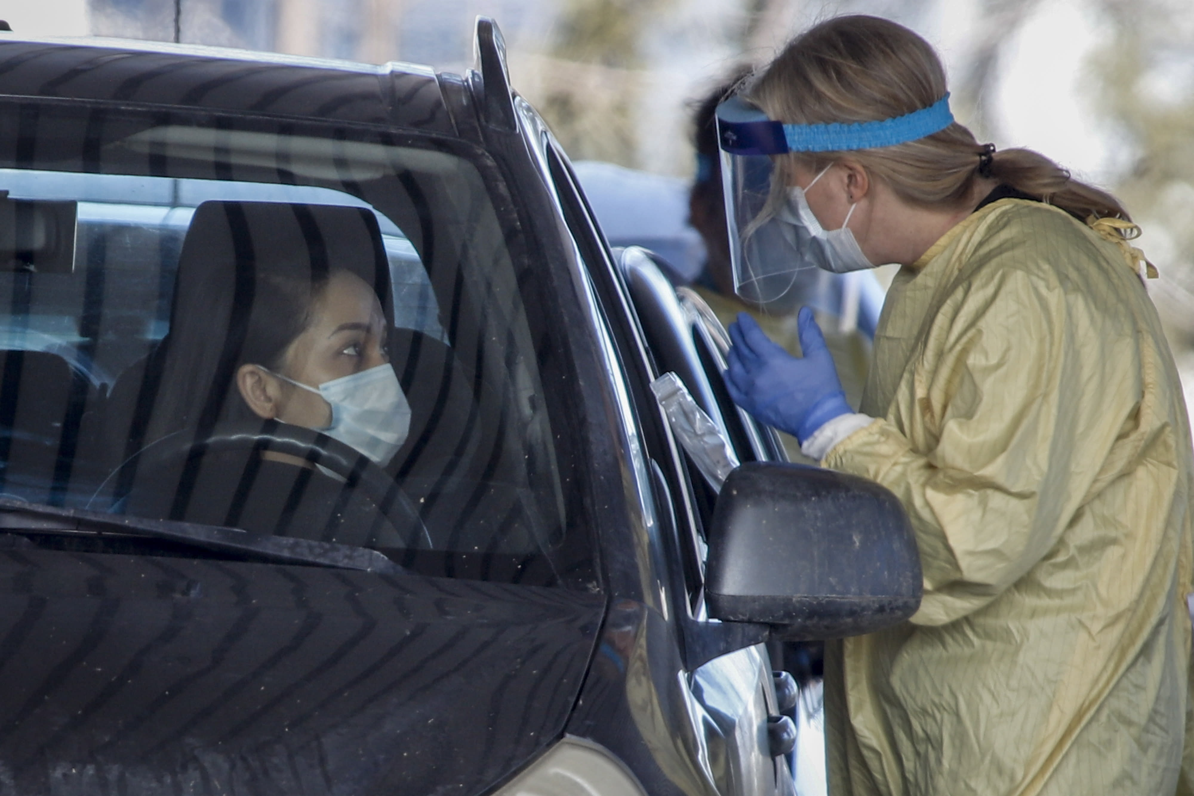 An Alberta Health Services employee speaks with a motorist at a drive-thru coronavirus testing facility in Calgary, Alberta, Friday, March 27, 2020. (Jeff McIntosh/The Canadian Press via AP)
