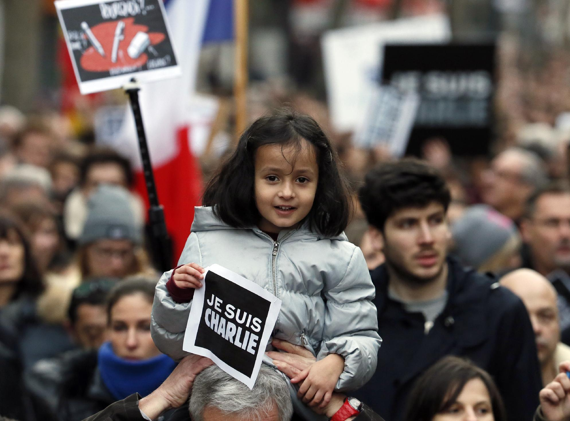 """A child holds a note reading """"Je suis Charlie (I am Charlie)"""" during a Unity rally """"Marche Republicaine"""" in Paris on January 11, 2015 in tribute to the 17 victims of a three-day killing spree by homegrown Islamists (AFP Photo/Patrick Kovarick)"""