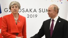Putin' a brave face on it! Picture of stoney-faced Theresa May and Russian leader captures tense meeting