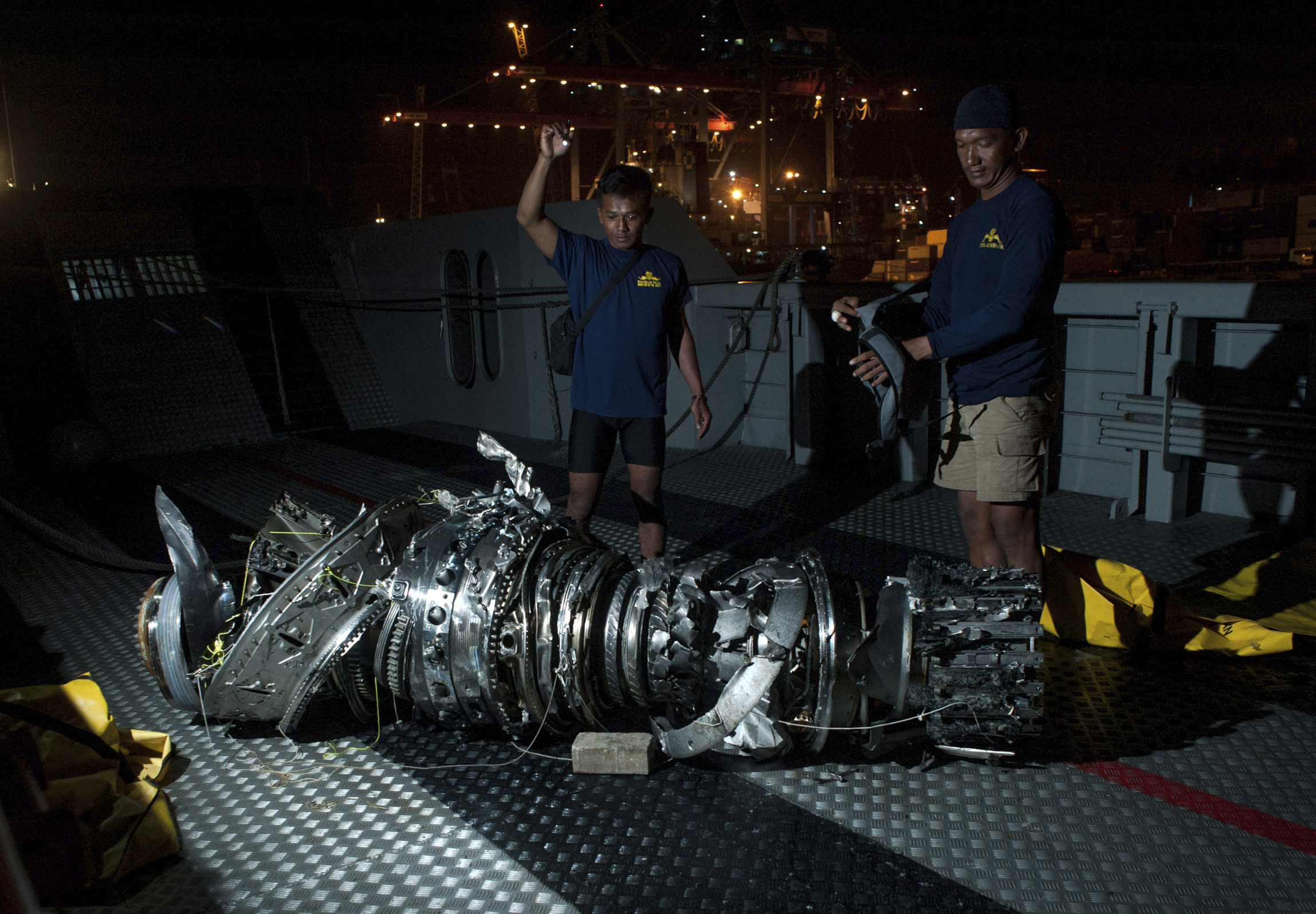 Navy divers inspect what is believed to be engine of the crashed Lion Air jet after it was retrieved from the sea floor, at Tanjung Priok Port in Jakarta, Indonesia, Saturday, Nov. 3, 2018. The brand new Boeing 737 MAX 8 jet plunged into the Java Sea just minutes after takeoff from Jakarta early on Oct. 29, killing all of its passengers on board. (AP Photo/Fauzy Chaniago)