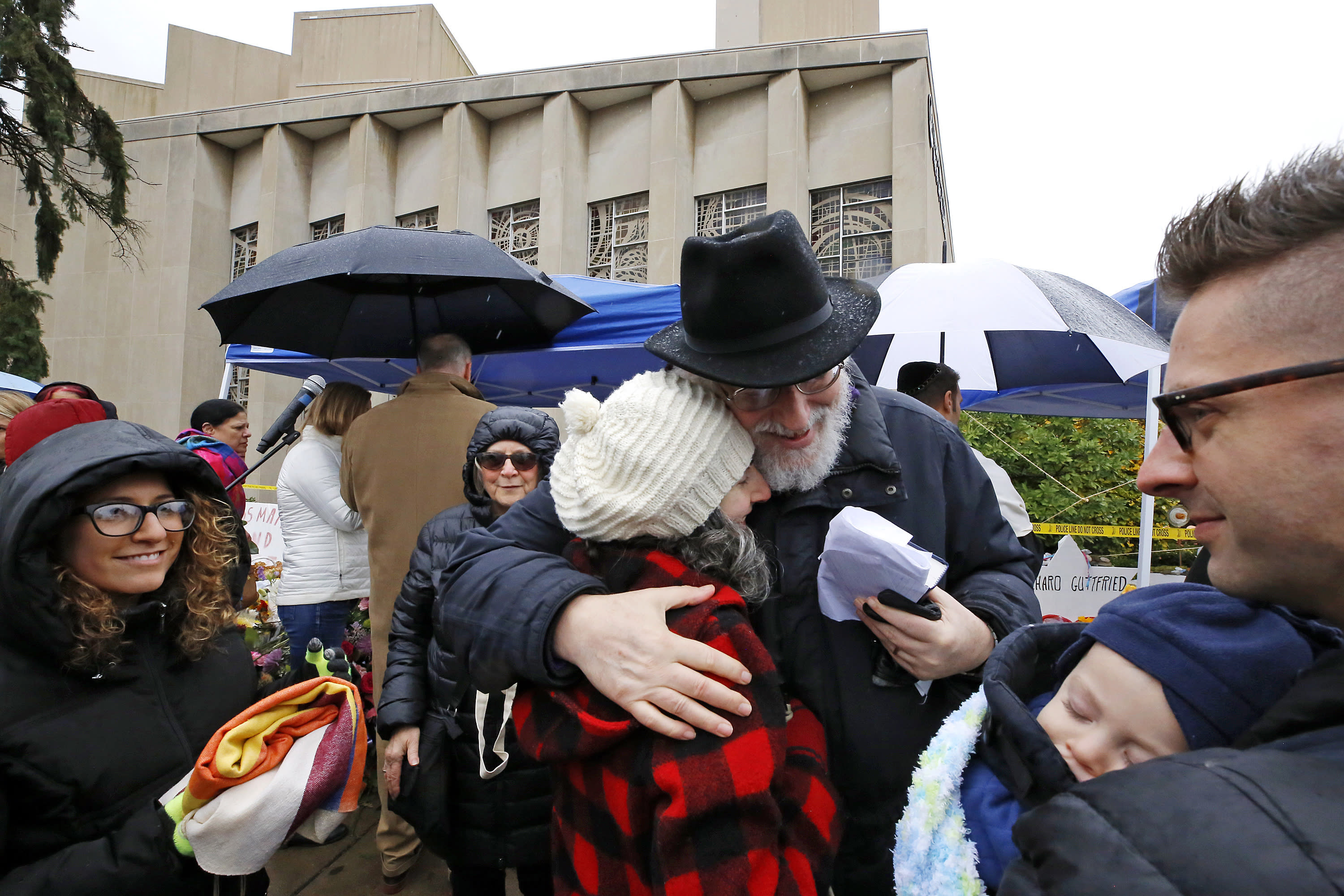 Rabbi Chuck Diamond, center, a former Rabbi at the Tree of Life Synagogue, hugs a woman after leading a Shabbat service outside the Tree of Life Synagogue, Saturday, Nov. 3, 2018 in Pittsburgh. Last Saturday, 11 people were killed and six wounded when their worship was interrupted by a gunman's bullets. (AP Photo/Gene J. Puskar)