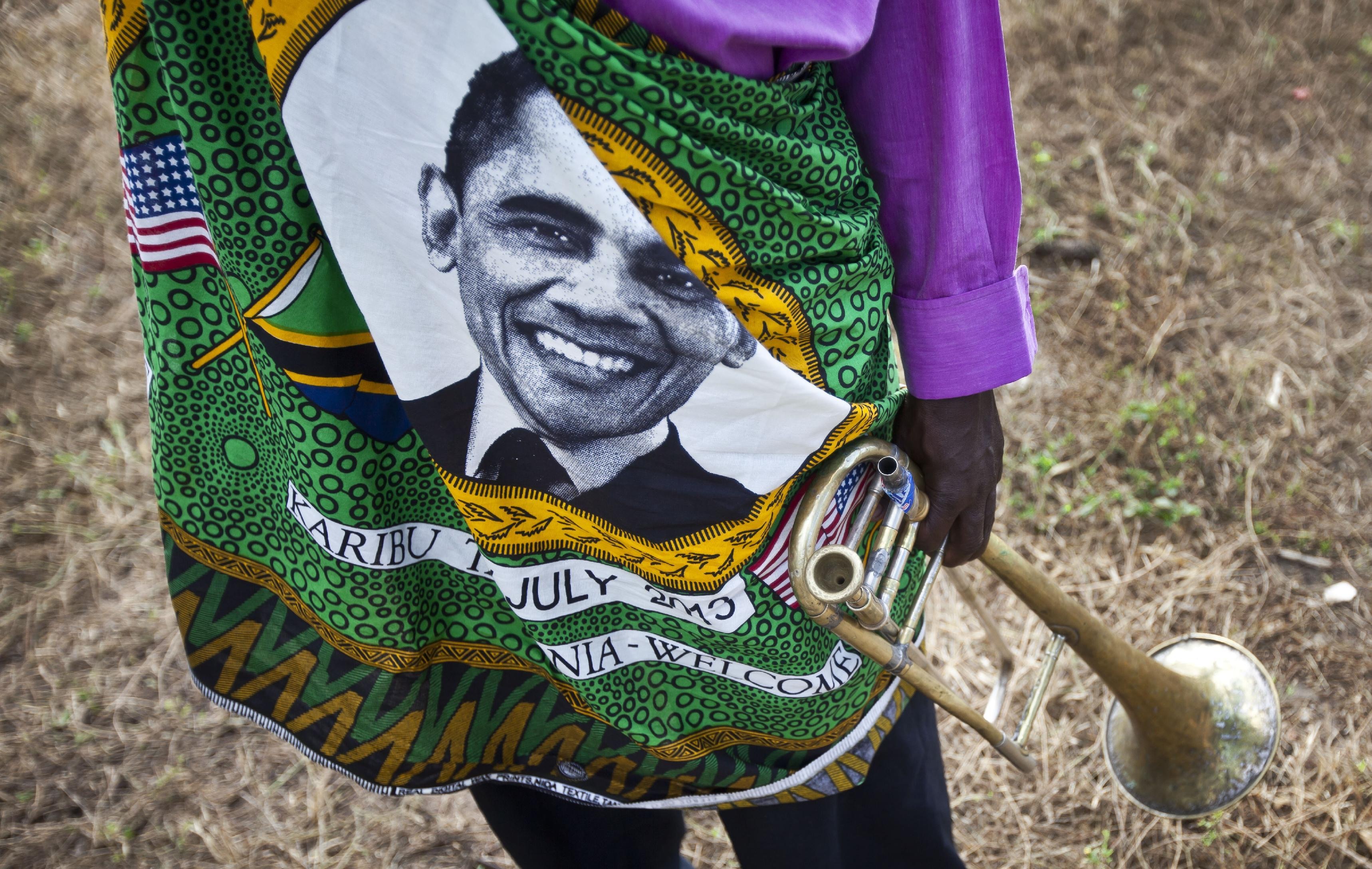 A member of the brass band that will welcome U.S. President Barack Obama stands on the road next to State House, wearing a shirt with the face of Obama, ahead of the meeting with Tanzanian President Jakaya Kikwete, at State House in Dar es Salaam, Tanzania Monday, July 1, 2013. The Democratic president was to fly Monday into Dar es Salaam, Tanzania, the last stop on a weeklong tour of Africa that wraps up Tuesday, while his Republican predecessor coincidentally also plans to be there for a conference on African women organized by the George W. Bush Institute. (AP Photo/Ben Curtis)