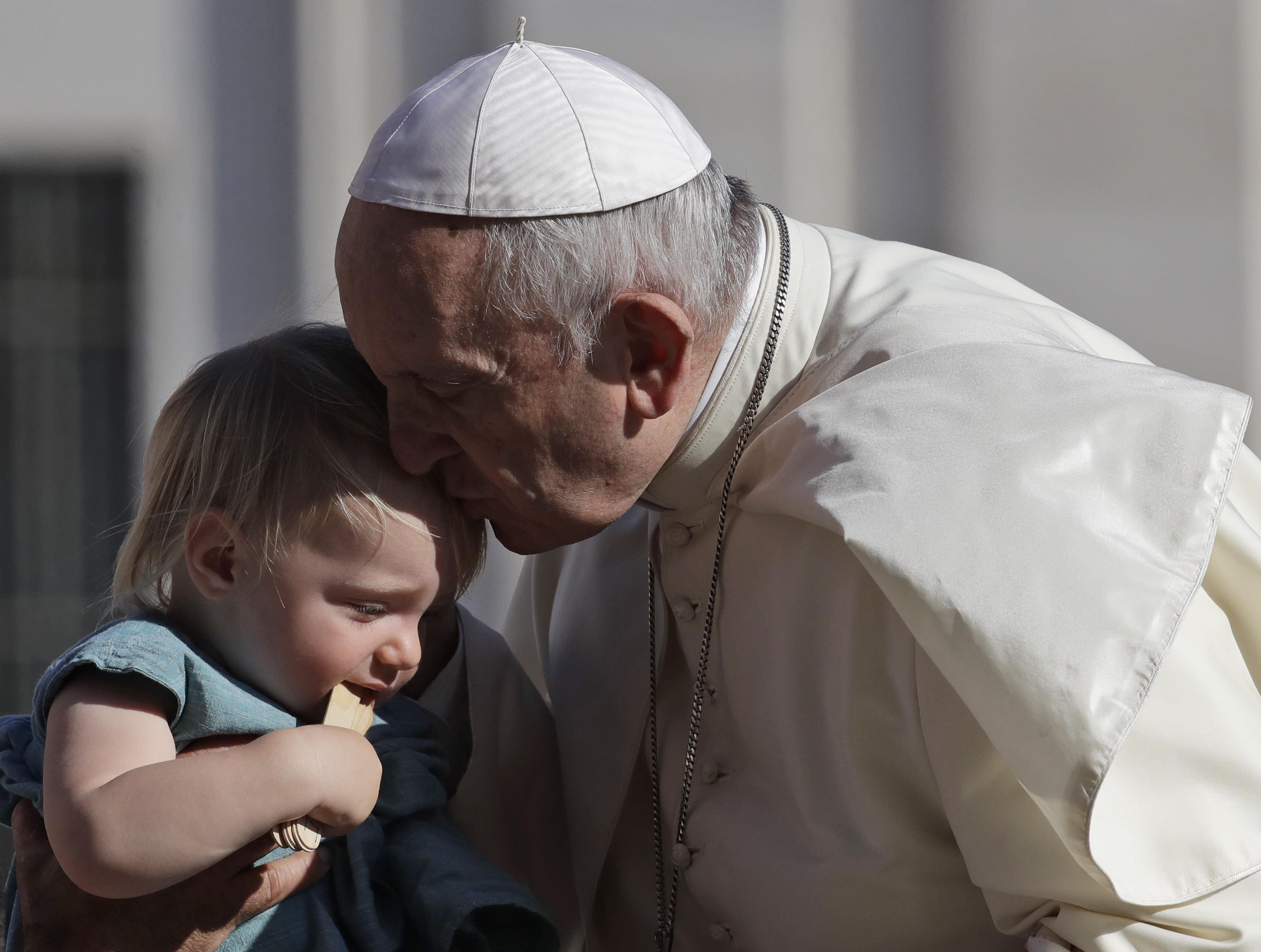 El papa Francisco besa a un niño al arribar a la plaza de San Pedro en el Vaticano para su audiencia general semanal, 5 de septiembre de 2018. (AP Foto/Alessandra Tarantino)