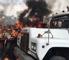 Venezuelan soldiers set fire to aid convoys as troops fire tear gas at protesters on Colombia border