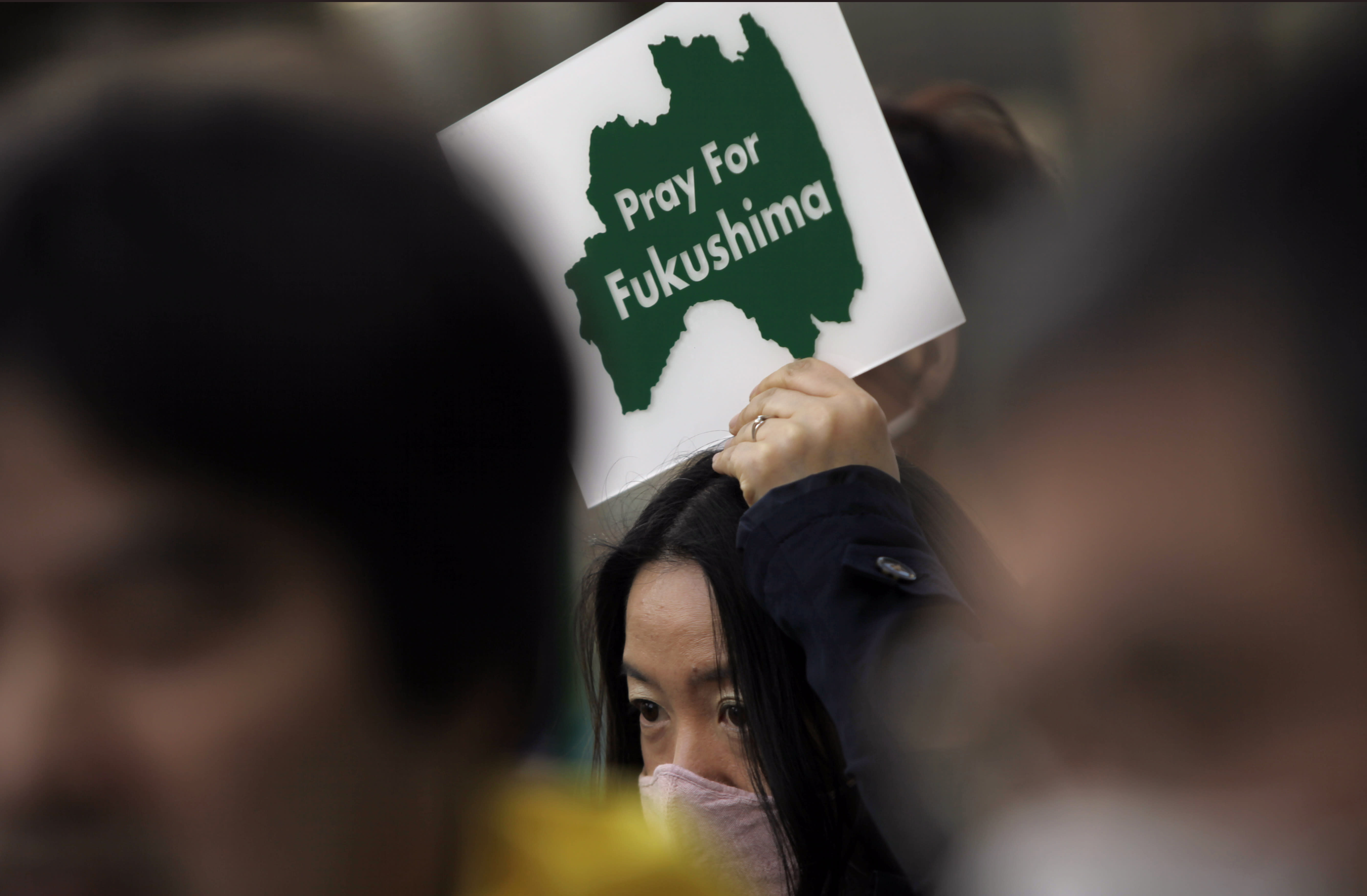 A protester holds a placard to pay tribute to the victims in Fukushima of the March 11, 2011 nuclear disaster following the earthquake and tsunami, during an anti-nuclear demonstration in Tokyo, Saturday, March 9, 2013. Gathering on a weekend ahead of the second anniversary of the March 11 quake and tsunami that sent Fukushima Dai-ichi plant into multiple meltdowns, demonstrators said they would never forget the world's worst nuclear catastrophe, and expressed alarm over the government's eagerness to restart reactors. (AP Photo/Junji Kurokawa)