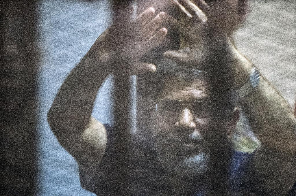 Egypt's deposed Islamist president Mohamed Morsi behind the defendant's cage as the judge reads out his verdict sentencing him and more than 100 other defendants to death at the police academy in Cairo on May 16, 2015 (AFP Photo/Khaled Desouki)