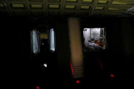 FILE PHOTO: A Metro subway system map can be seen in a train car window as the train leaves the station during the morning rush at the Metro Center subway station in Washington