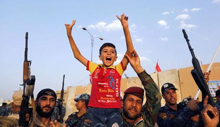 Members of Iraqi Federal Police carry a boy as they celebrate victory of military operations against the Islamic State militants in West Mosul, Iraq July 2, 2017. REUTERS/Erik De Castro