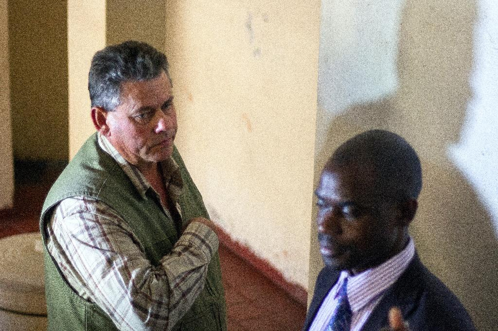 Zimbabwean hunter Theo Bronkhorst (left) and his defence lawyer wait outside the Magistrate's Court in Hwange, on July 29, 2015 (AFP Photo/Zinyange Auntony)