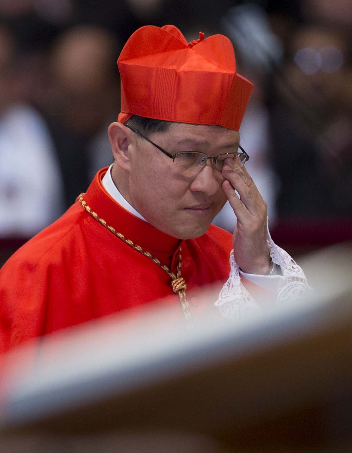 Newly elected Cardinal Luis Antonio Tagle, Archbishop of Manila, Philippines, wipes his eyes after he received the red three-cornered biretta hat from Pope Benedict XVI during a consistory in St. Peter's Basilica at the Vatican, Saturday, Nov. 24, 2012. Six new cardinals are joining the elite club of churchmen who will elect the next pope, bringing a more geographically diverse mix into the European-dominated College of Cardinals. (AP Photo/Andrew Medichini)