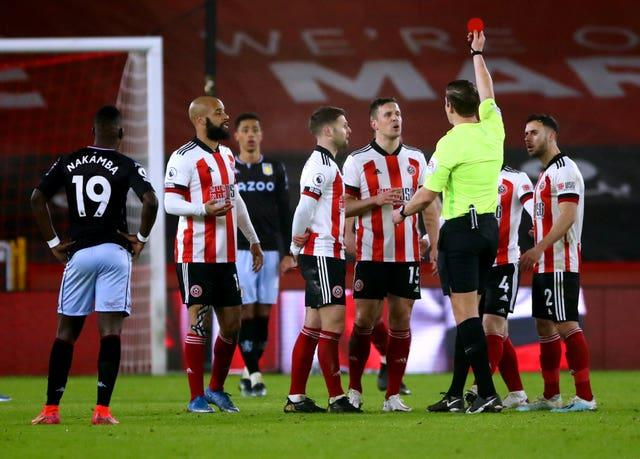 Sheffield United's Phil Jagielka (centre right) sees his yellow card upgraded to a red card after referee Robert Jones consults the VAR