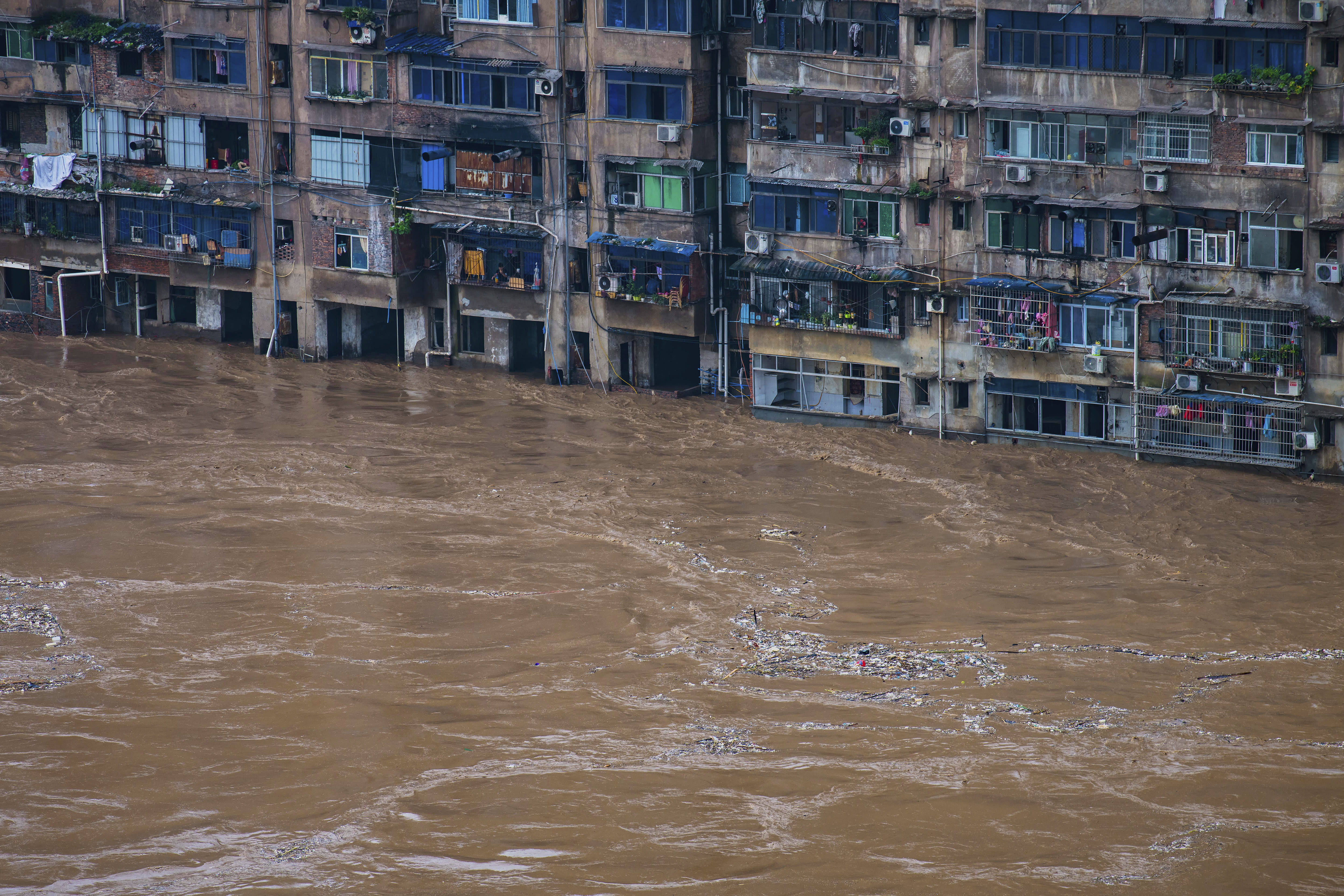 In this photo released by Xinhua News Agency, floodwaters flow past a residential building in Qijiang District of Chongqing Municipality, southwest China on July 1, 2020. A wide swath of southern China braced Sunday, July 5, 2020 for more seasonal rains and flooding. (Chen Xingyu/Xinhua via AP)