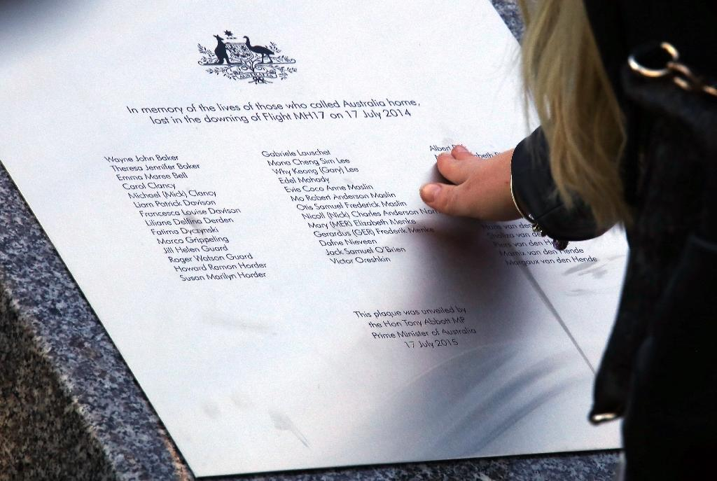 A relative of an Australian victim of the Malaysia Airlines flight MH17 disaster touches a memorial unveiled outside Parliament House in Canberra on July 17, 2015 (AFP Photo/David Gray)