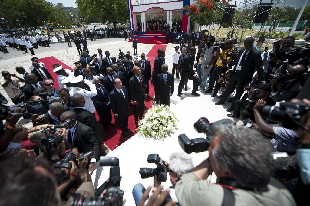French President Francois Hollande (C-left) and President of Haiti Michel Martelly (C-right) place a wreath at the Toussaint Louverture Statue in Port-au-Prince on May 12, 2015 (AFP Photo/Hector Retamal)