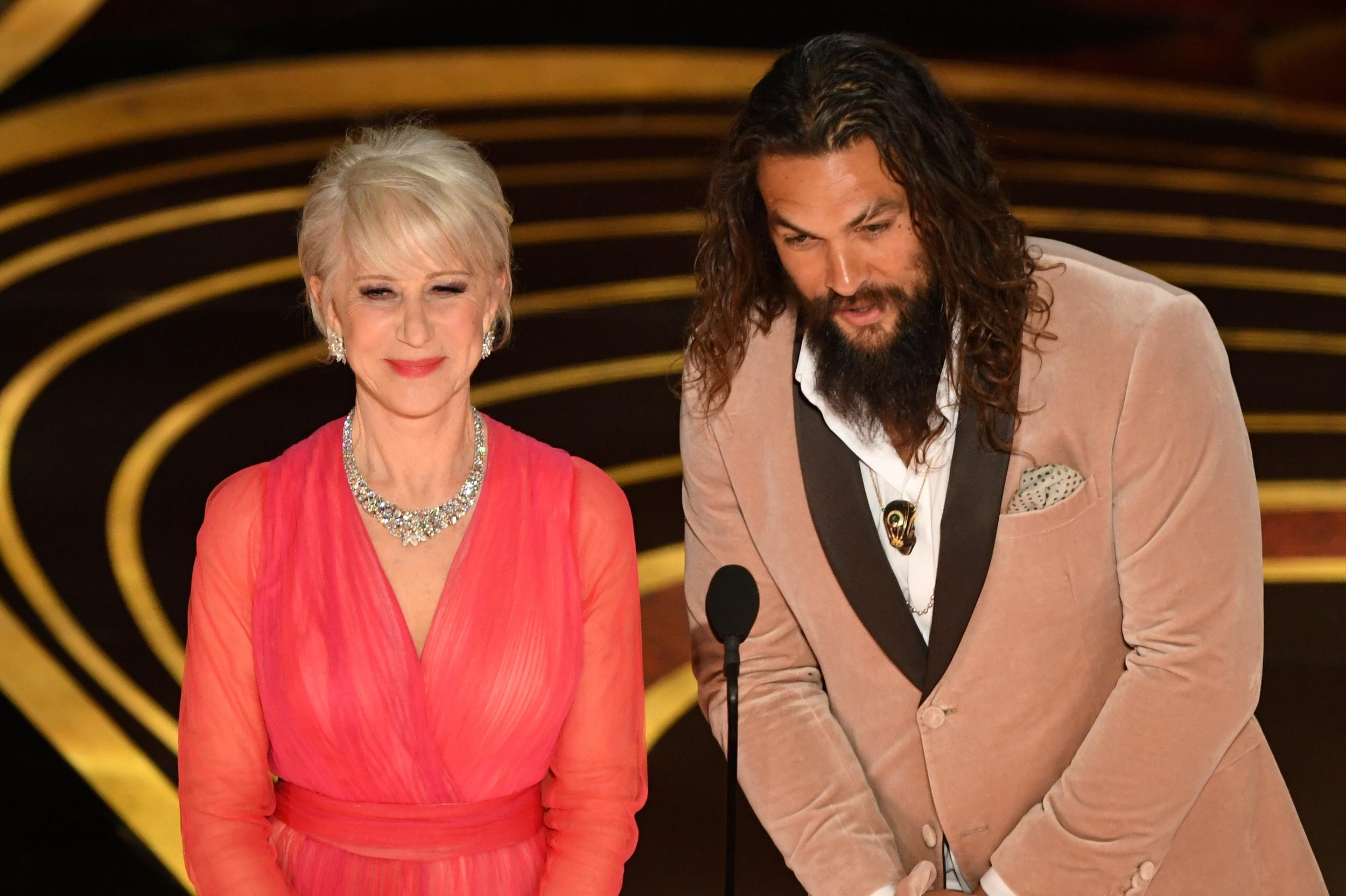 British actress Helen Mirren and actor Jason Mamoa present an award during the 91st Annual Academy Awards at the Dolby Theatre in Hollywood, California on February 24, 2019. (Photo by VALERIE MACON / AFP)        (Photo credit should read VALERIE MACON/AFP/Getty Images)
