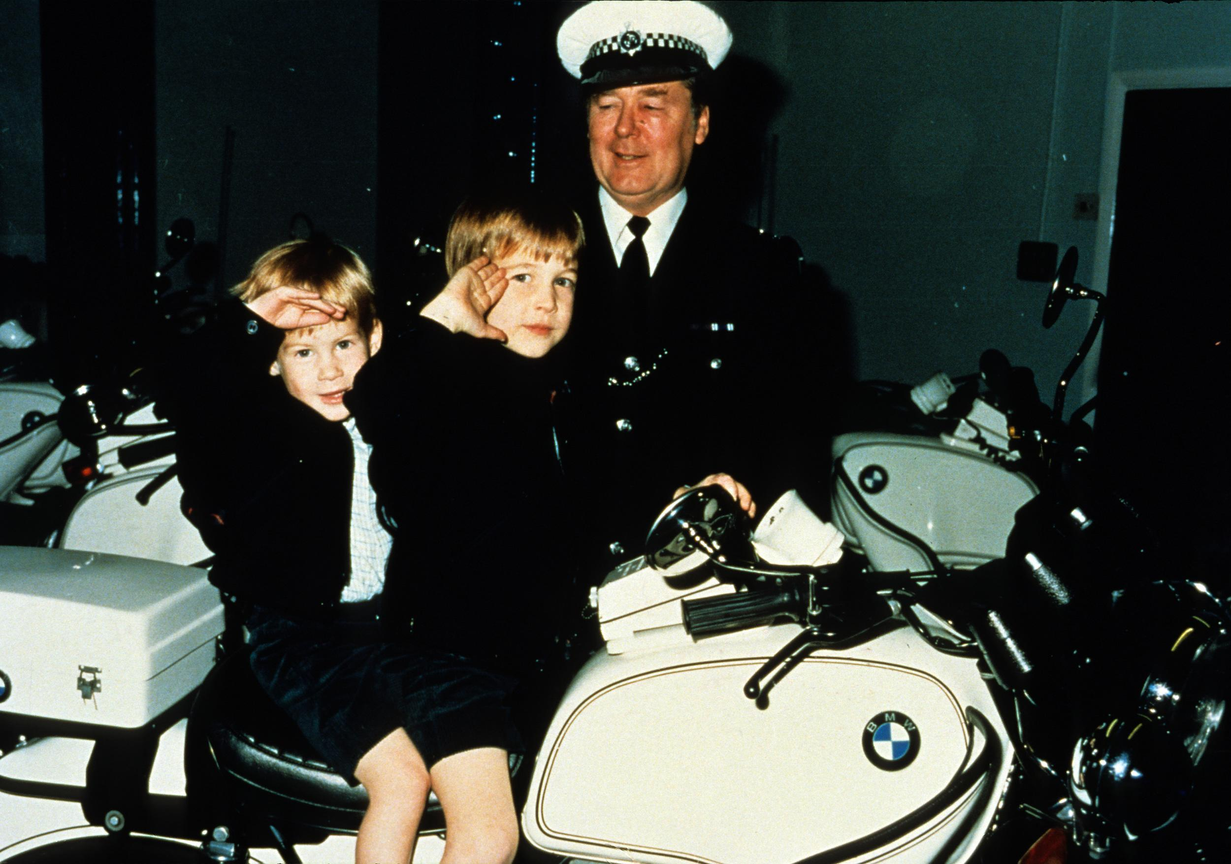 WINDOSR- NOVEMBER: (FILE PHOTO)  Prince William and Prince Harry  give a royal salute from atop a police motorbike during a visit to the poloice force in November 1987 in Windsor, England.   (Photo by Anwar Hussein/Getty Images)