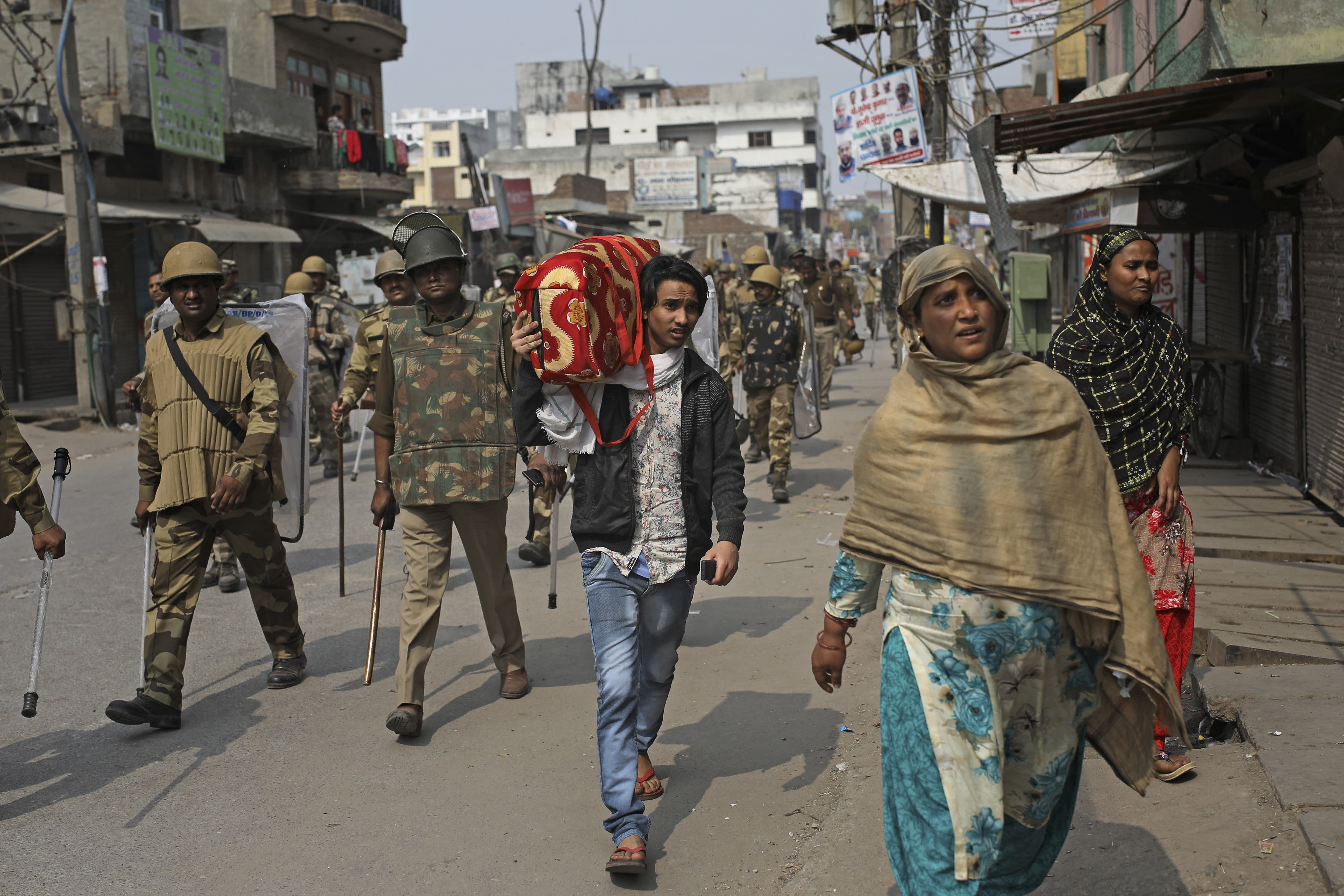 An Indian Muslim family leaves the area as Indian paramilitary soldiers patrol a street vandalized in Tuesday's violence in New Delhi, India, Thursday, Feb. 27, 2020. India accused a U.S. government commission of politicizing communal violence in New Delhi that killed at least 30 people and injured more than 200 as President Donald Trump was visiting the country. The violent clashes between Hindu and Muslim mobs were the capital's worst communal riots in decades and saw shops, Muslim shrines and public vehicles go up in flames. (AP Photo/Altaf Qadri)