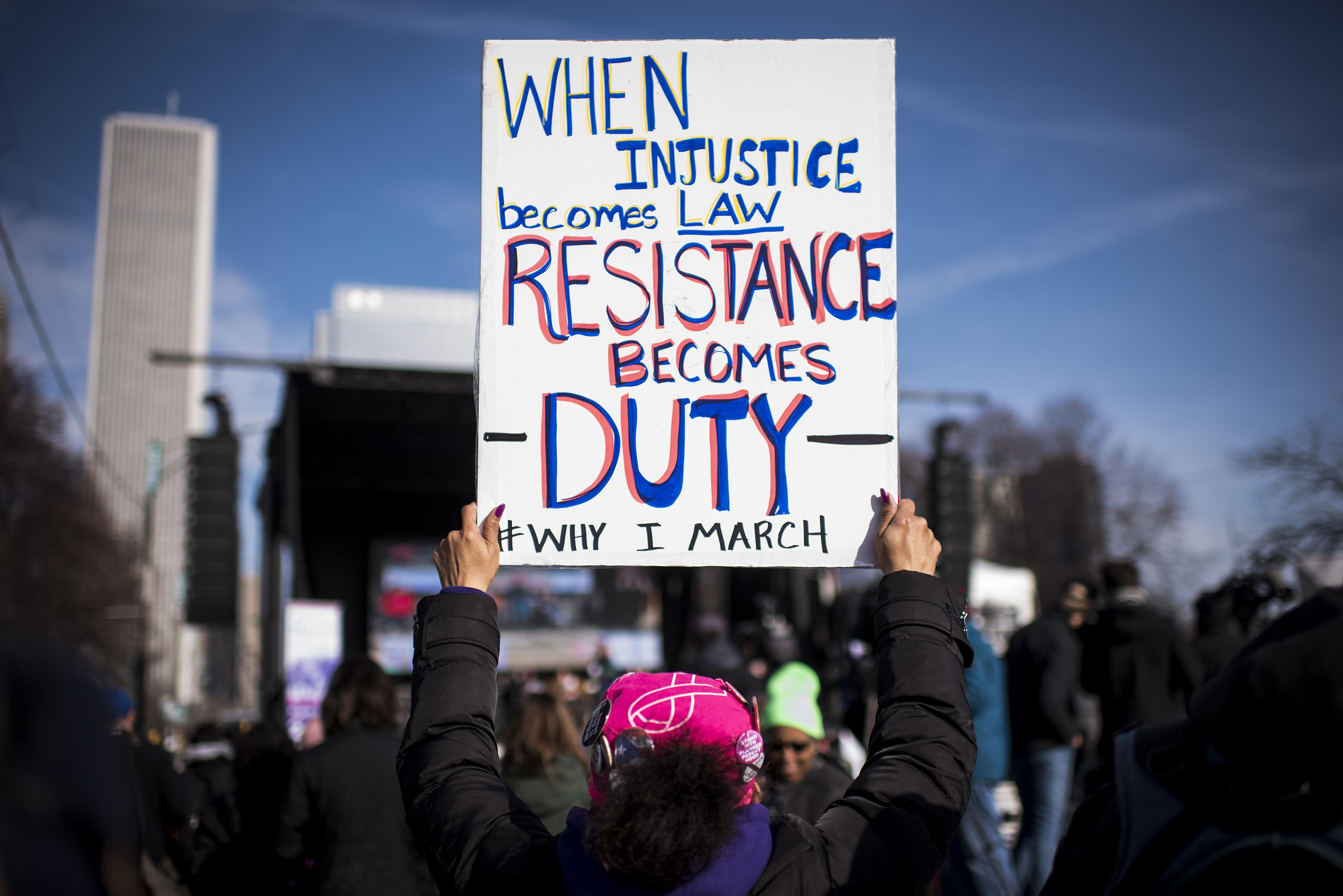 """<p>A demonstrator holds a sign that reads """"When Injustice Becomes Law, Resistance Becomes Duty"""" during the second annual Women's March in Chicago, Ill., on Saturday, Jan. 20, 2018. (Photo: Christopher Dilts/Bloomberg via Getty Images) </p>"""