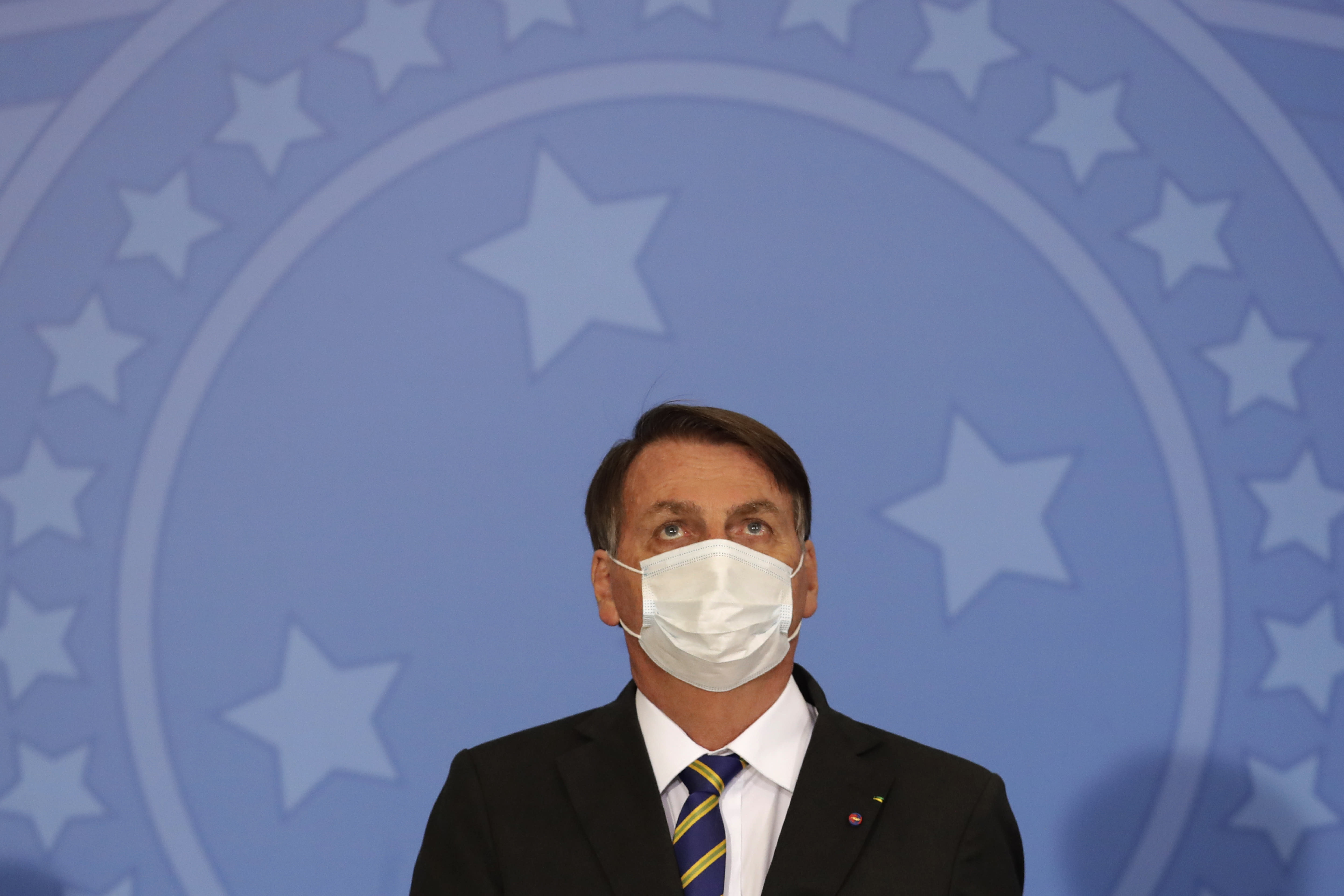 Brazil's President Jair Bolsonaro wearing a protective mask to curb the spread of the new coronavirus, attends the launching ceremony of a rights guarantee program for rural women, at the Planalto Presidential Palace in Brasilia, Brazil, Wednesday, July 29, 2020. (AP Photo/Eraldo Peres)