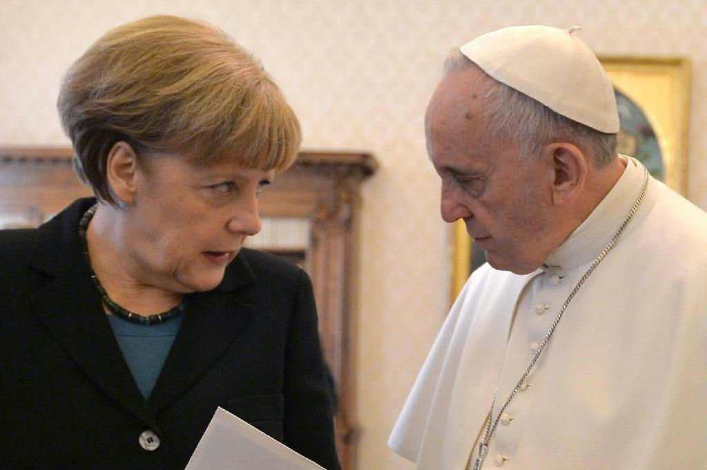 Pope Francis speaks with Angela Merkel during a 2015 meeting at the Vatican