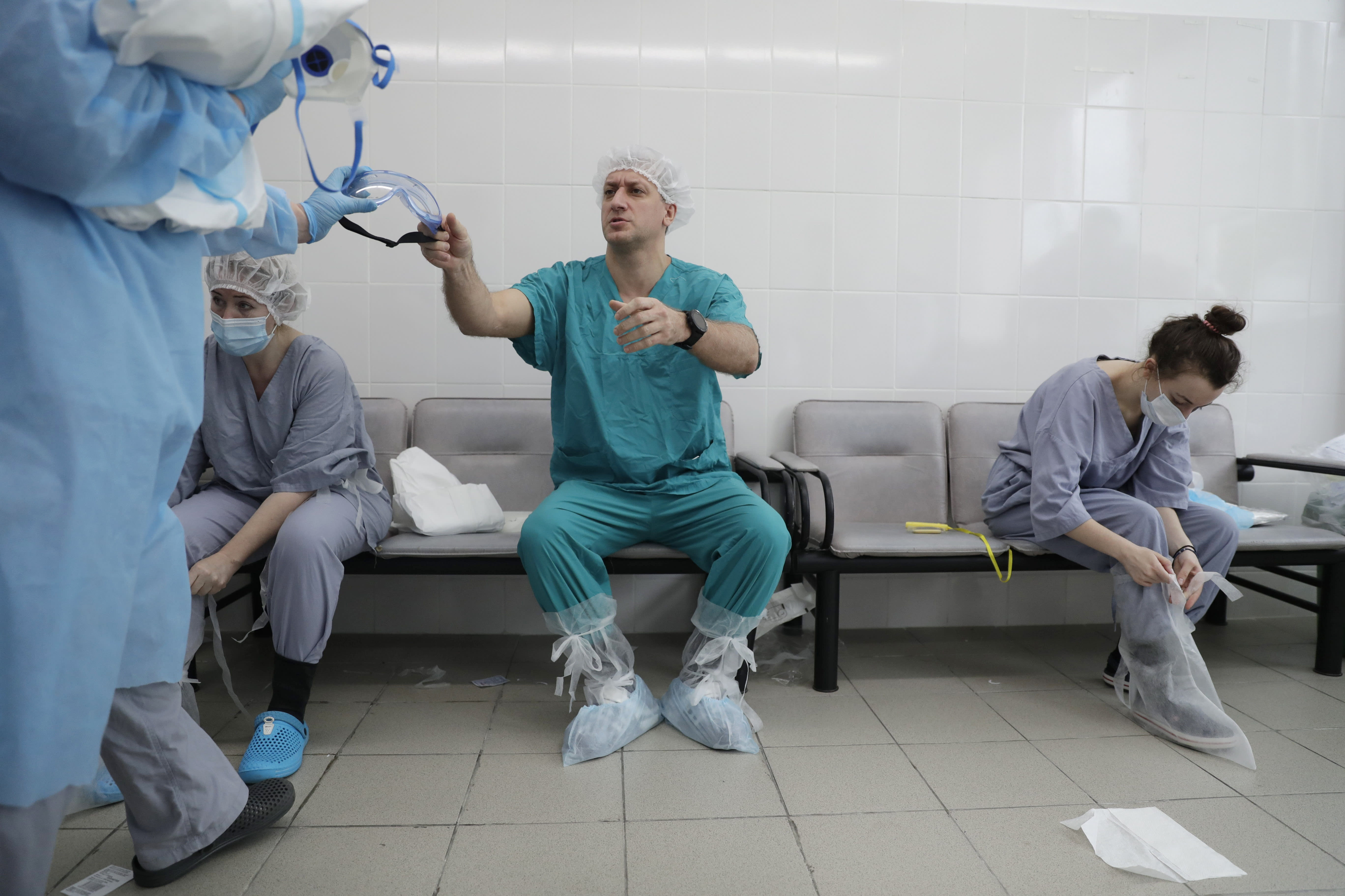 In this photo taken on Friday, May 15, 2020, Dr. Osman Osmanov, center, puts on protective gear before his shift at an intensive care unit of the Filatov City Clinical Hospital in Moscow, Russia. Moscow accounts for about half of all of Russia's coronavirus cases, a deluge that strains the city's hospitals and has forced Osmanov to to work every day for the past two months, sometimes for 24 hours in a row. (AP Photo/Pavel Golovkin)
