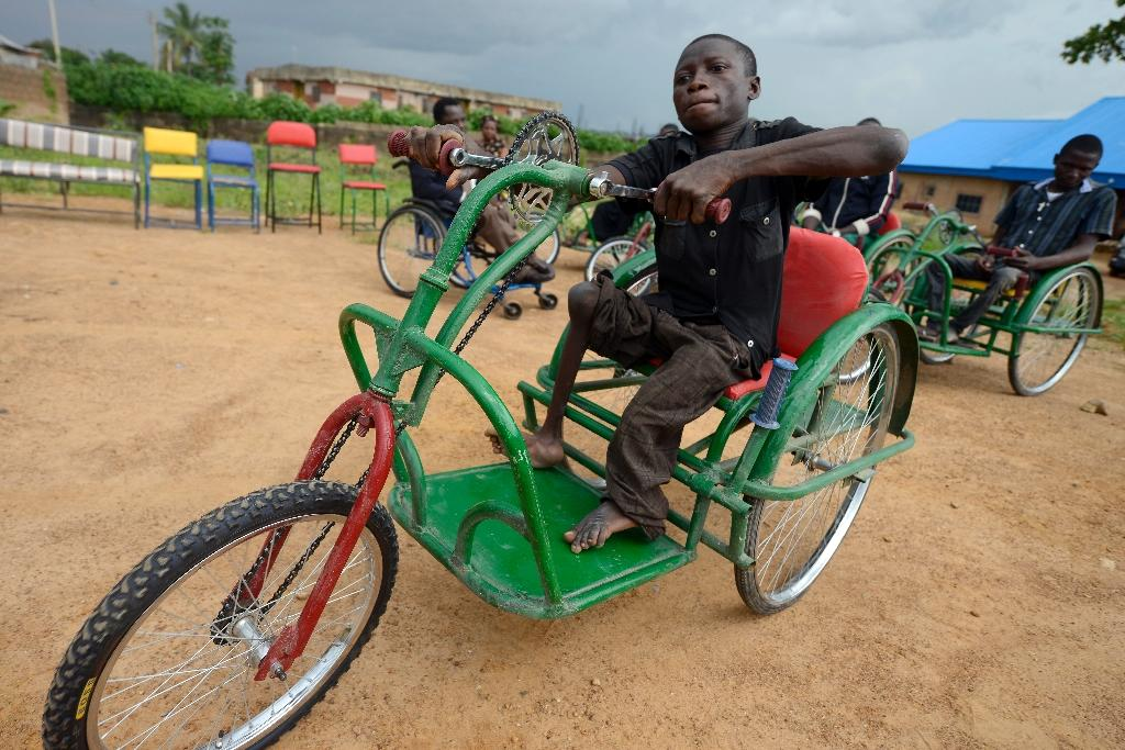 Handicapped Jacob Clement rides on his new wheelchair at the Beautiful Gate Handicapped People's Centre in Jos, northcentral Nigeria Plateau State, on July 16, 2015 (AFP Photo/Pius Utomi Ekpei)