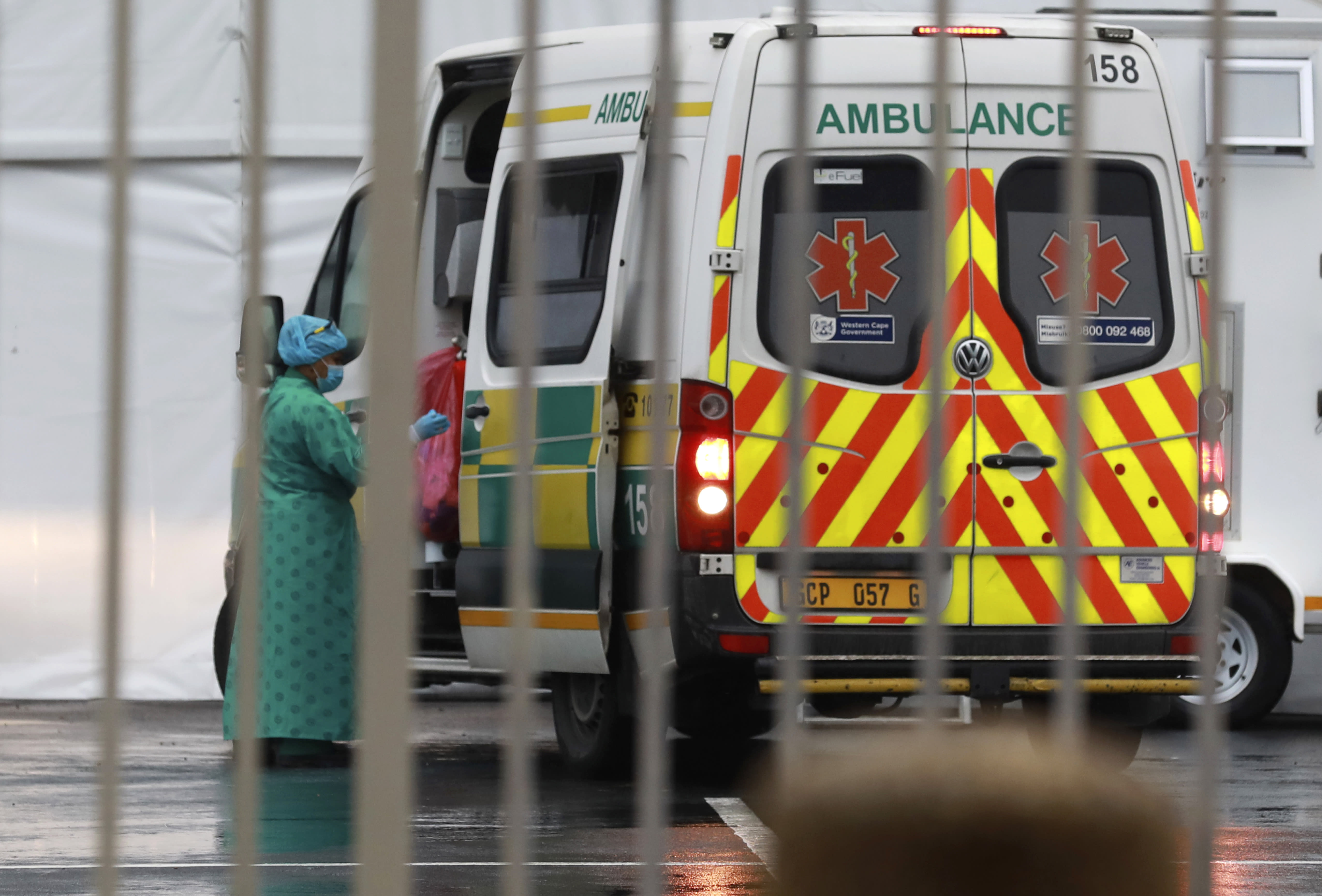 A health worker enters an ambulance outside the COVID-19 field hospital created in the International Convention Centre in Cape Town, South Africa, Monday, June 29, 2020. South Africa's reported coronavirus are surging. Its hospitals are now bracing for an onslaught of patients, setting up temporary wards and hoping advances in treatment will help the country's health facilities from becoming overwhelmed. (AP Photo/Nardus Engelbrecht)