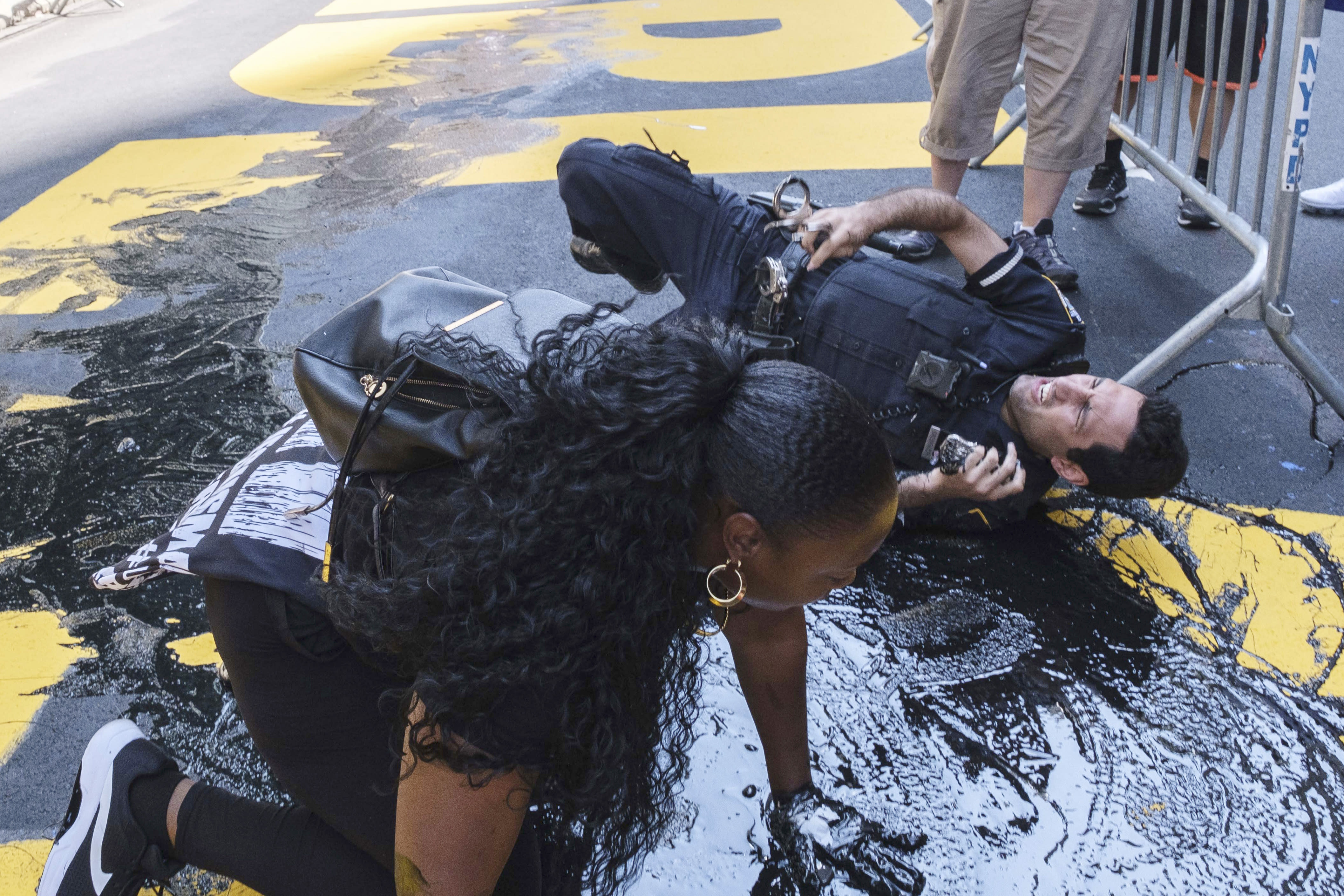 An NYPD officer falls during an attempt to detain a protester pouring black paint on the Black Lives Matter mural outside of Trump Tower on Fifth Avenue in the Manhattan borough of New York on Saturday, July 18, 2020. (AP Photo/Yuki Iwamura)