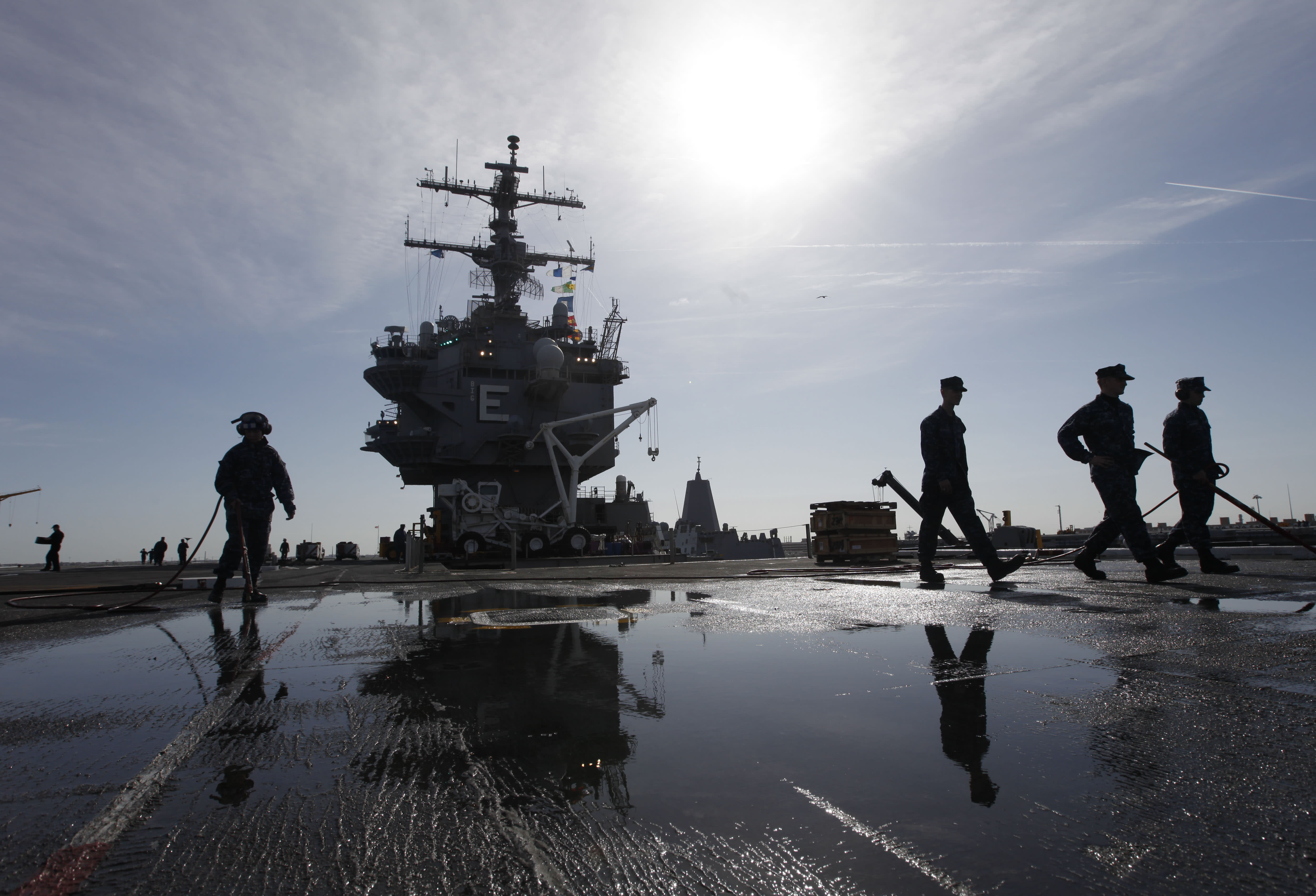 FILE - In this March 8, 2012 file photo, sailors clean the flight deck as they move supplies and equipment in preparation for the final deployment of the nuclear aircraft carrier USS Enterprise at the Norfolk Naval Station in Norfolk, Va. The U.S. Navy said Monday, April 9, 2012 that it has deployed a second aircraft carrier to the Persian Gulf region amid rising tensions with Iran over its nuclear program. The deployment of the nuclear-powered USS Enterprise along the Abraham Lincoln carrier strike group marks only the fourth time in the past decade that the Navy has had two aircraft carriers operating at the same time in the Persian Gulf and the Arabian Sea, said Cmdr. Amy Derrick-Frost of the Bahrain-based 5th Fleet. (AP Photo/Steve Helber, File)
