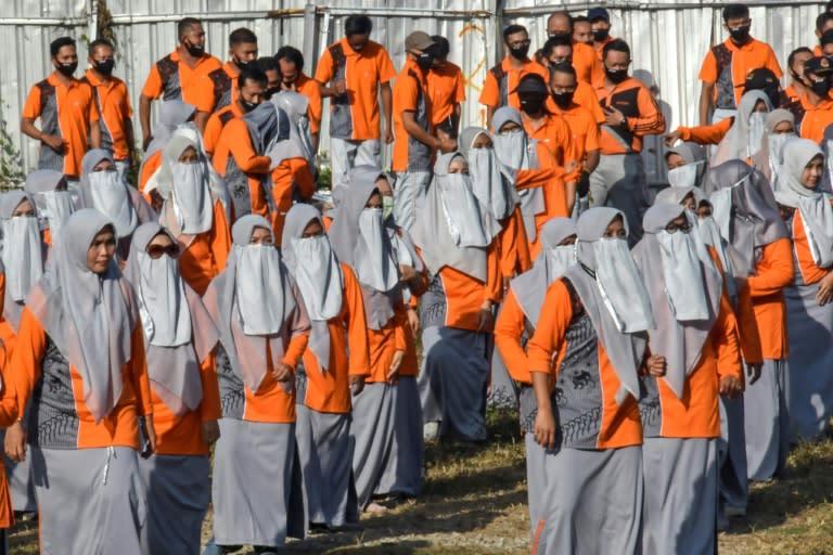Female civil servants do morning exercises in Lombok, wearing veils instead of masks, while men don masks behind them (AFP Photo/MOH EL SASAKY)