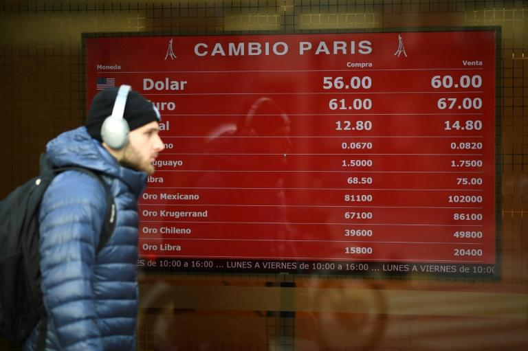 Currency exchange values are displayed on the buy-sell board of a money changer in Buenos Aires on August 13, 2019 after the Argentine peso plunged in value before halting its slide two days later