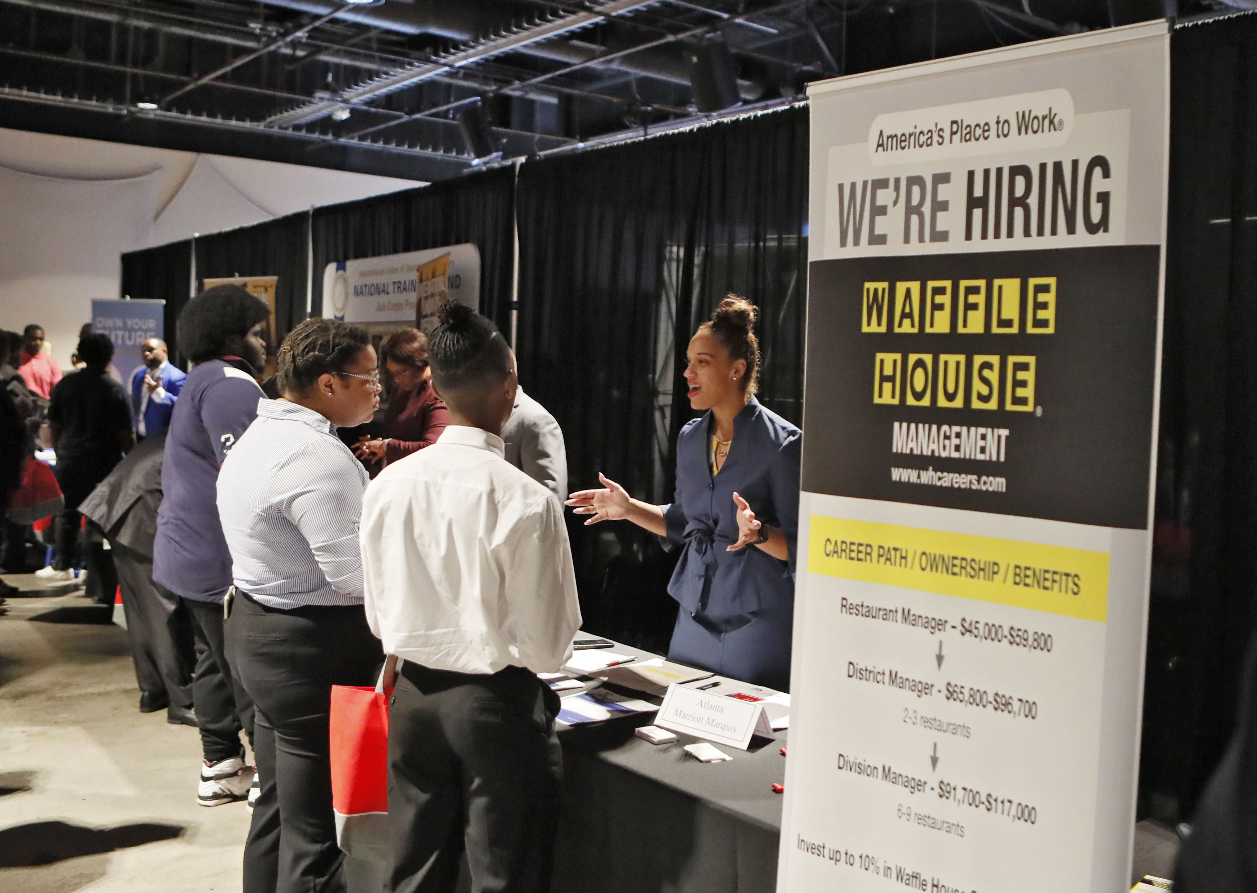 FILE - In this Aug. 14, 2019, file photo a Waffle House representative speaks to potential applicants during a job and resource fair in Atlanta. On Friday, Sept. 6, the U.S. government issues the August jobs report. (Bob Andres/Atlanta Journal-Constitution via AP, File)