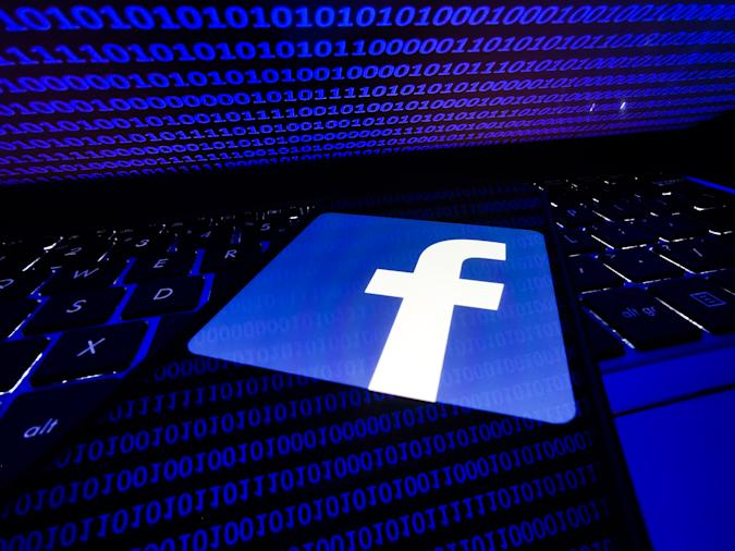 Facebook logo displayed on a phone screen is seen with binary code displayed on a laptop screen in this illustration photo taken in Krakow, Poland on August 17, 2021. (Photo by Jakub Porzycki/NurPhoto via Getty Images)