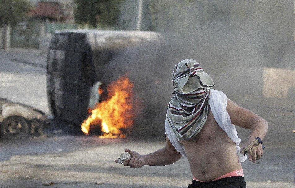 A masked Palestinian youth throws a rock during clashes with Israeli security forces in east Jerusalem on October 30, 2014 (AFP Photo/Ahmad Gharabli)