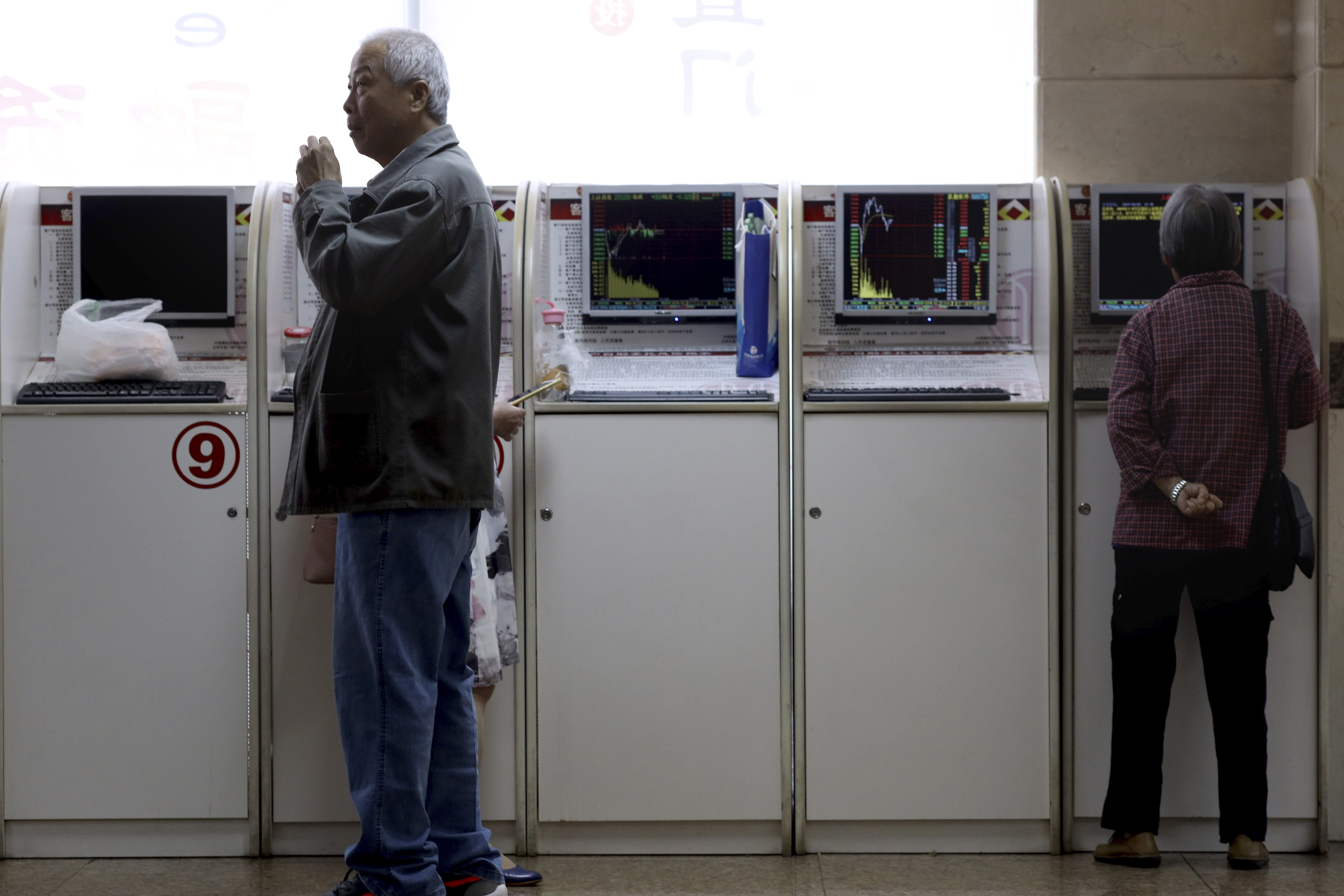 Chinese investors monitor stock prices at a brokerage in Beijing on Wednesday, Oct. 9, 2019. Shares slipped in Asia on Wednesday as tensions between the U.S. and China flared ahead of talks aimed at resolving the trade war between the world's two biggest economies. (AP Photo/Ng Han Guan)