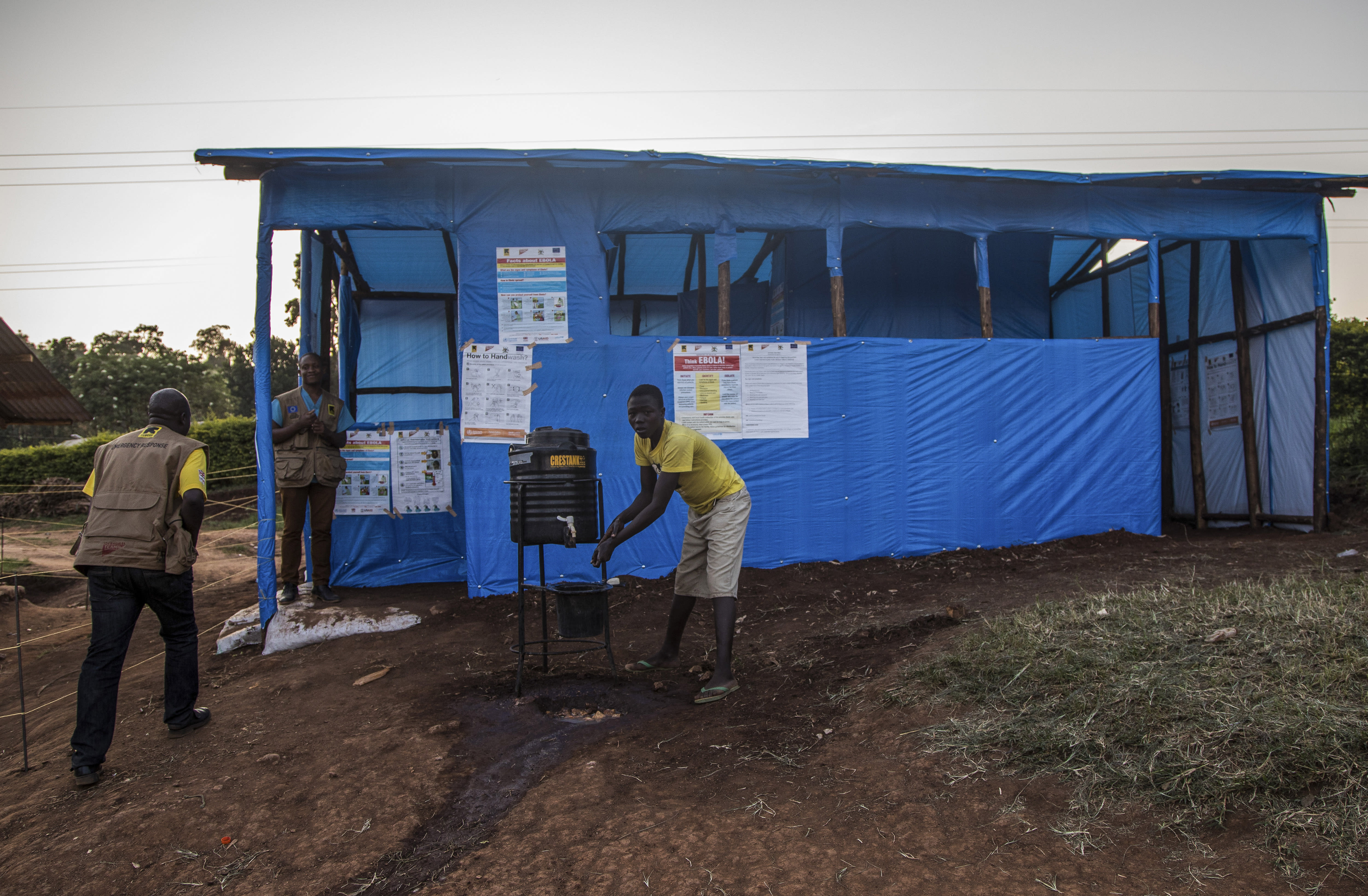 This photo released by the International Rescue Committee (IRC) shows a Congolese refugee boy washing his hands before entering one of the medical tents used for evaluating newly arrived Congolese for potential symptoms of Ebola, at the Kyaka refugee settlement in western Uganda Wednesday, June 12, 2019. A 5-year-old boy in Uganda vomiting blood became the first cross-border victim in the current Ebola outbreak on Wednesday, while his 3-year-old brother and grandmother tested positive for the disease that has killed nearly 1,400 people in Congo. (Kellie Ryan/International Rescue Committee via AP)