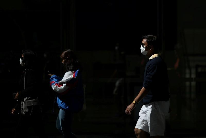 FILE PHOTO: Pedestrians wear protective face masks amidst fears of the coronavirus disease (COVID-19) in Sydney