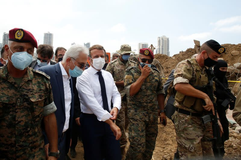 French President Emmanuel Macron gestures as he visits the devastated site of the explosion at the port of Beirut