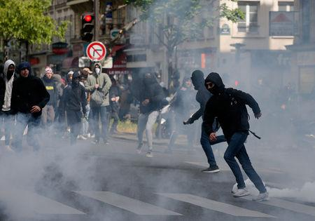 Hooded youths run through clouds of tear gas during clashes at a demonstration to protest the results of the first round of the presidential election in Paris, France, April 27, 2017. REUTERS/Gonzalo Fuentes