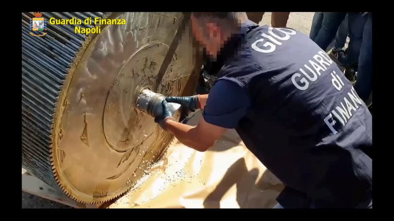An undated handout image shows an Italian finance police officer opening a machinery that contains ISIS produced amphetamine pills in Salerno